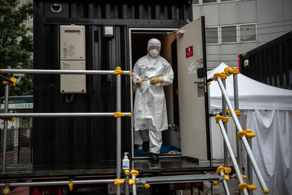 A nurse in full personal protective equipment walks from a changing room during a coronavirus (COVID-19) polymerase chain reaction (PCR) demonstration test in Tokyo, Japan on July 14, 2020.