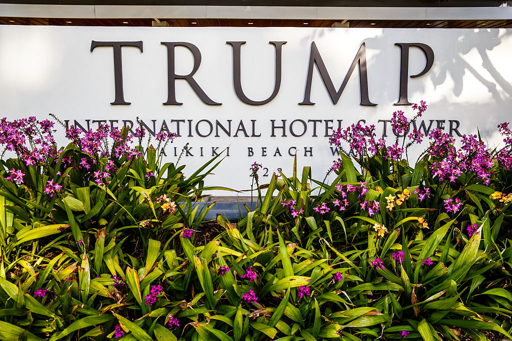 Tropical flowers and front entrance sign of Trump International Hotel Waikiki Beach. Five Star luxury hotel & residences owned by Donald Trump