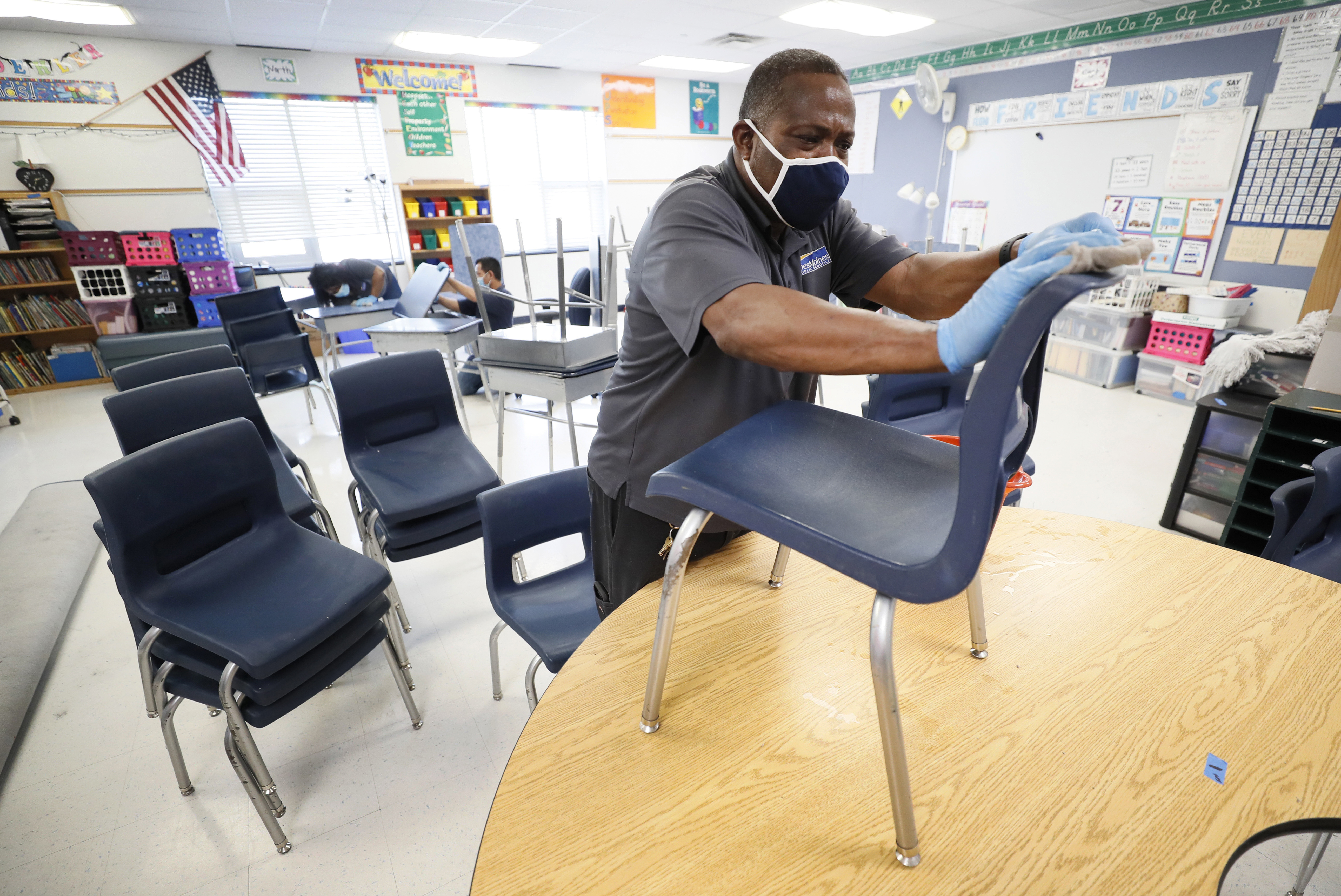 Custodian Tracy Harris cleans chairs in a classroom at Brubaker Elementary School in Des Moines, Iowa ON July 8, 2020.