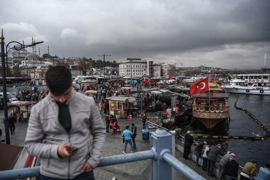 A man looks at his smartphone next to fish and bread vendors on Galata bridge in Istanbul's Eminonu district on November 6, 2018.