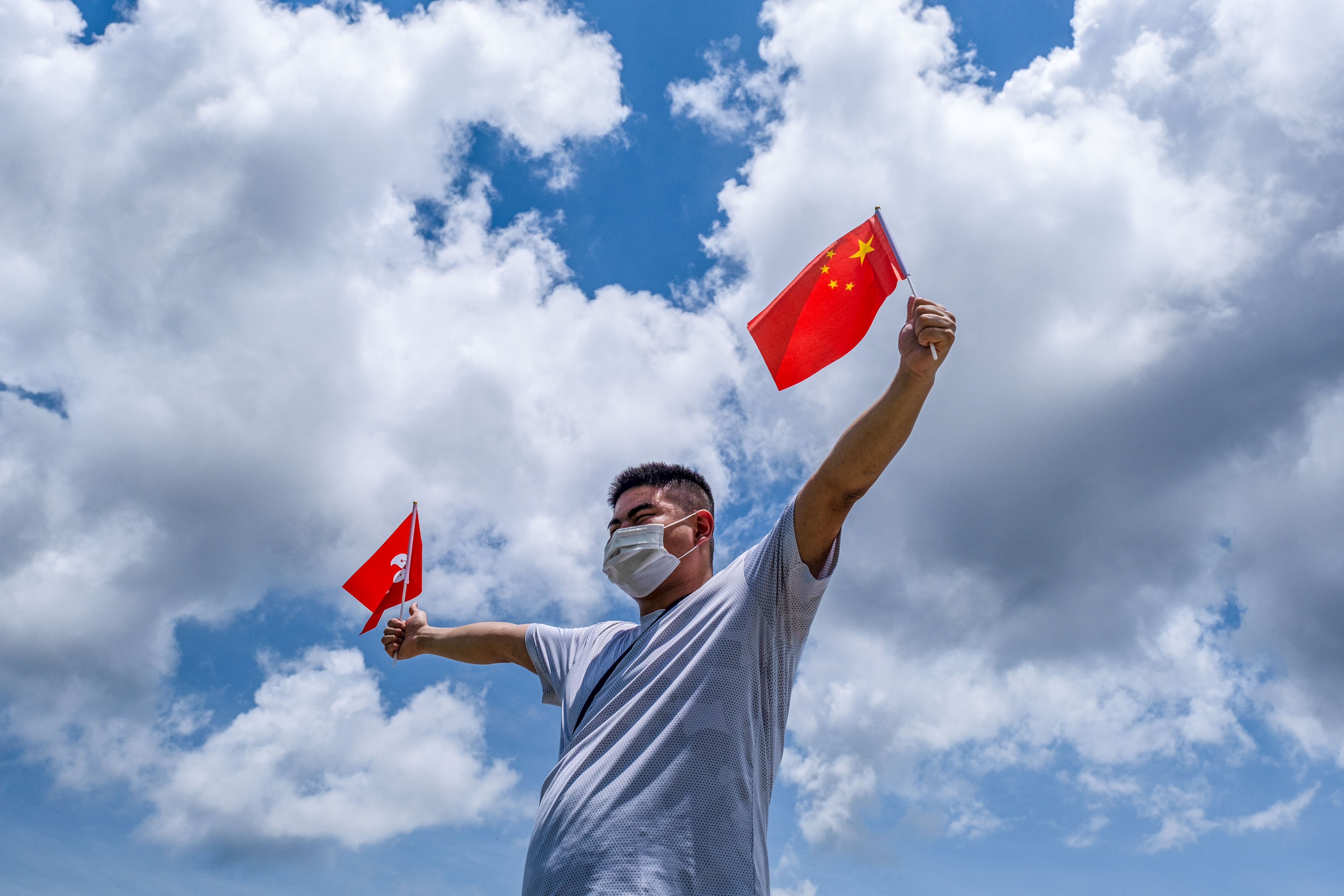A pro-China supporter waves Chinese and Hong Kong flags during a rally on June 30, 2020.