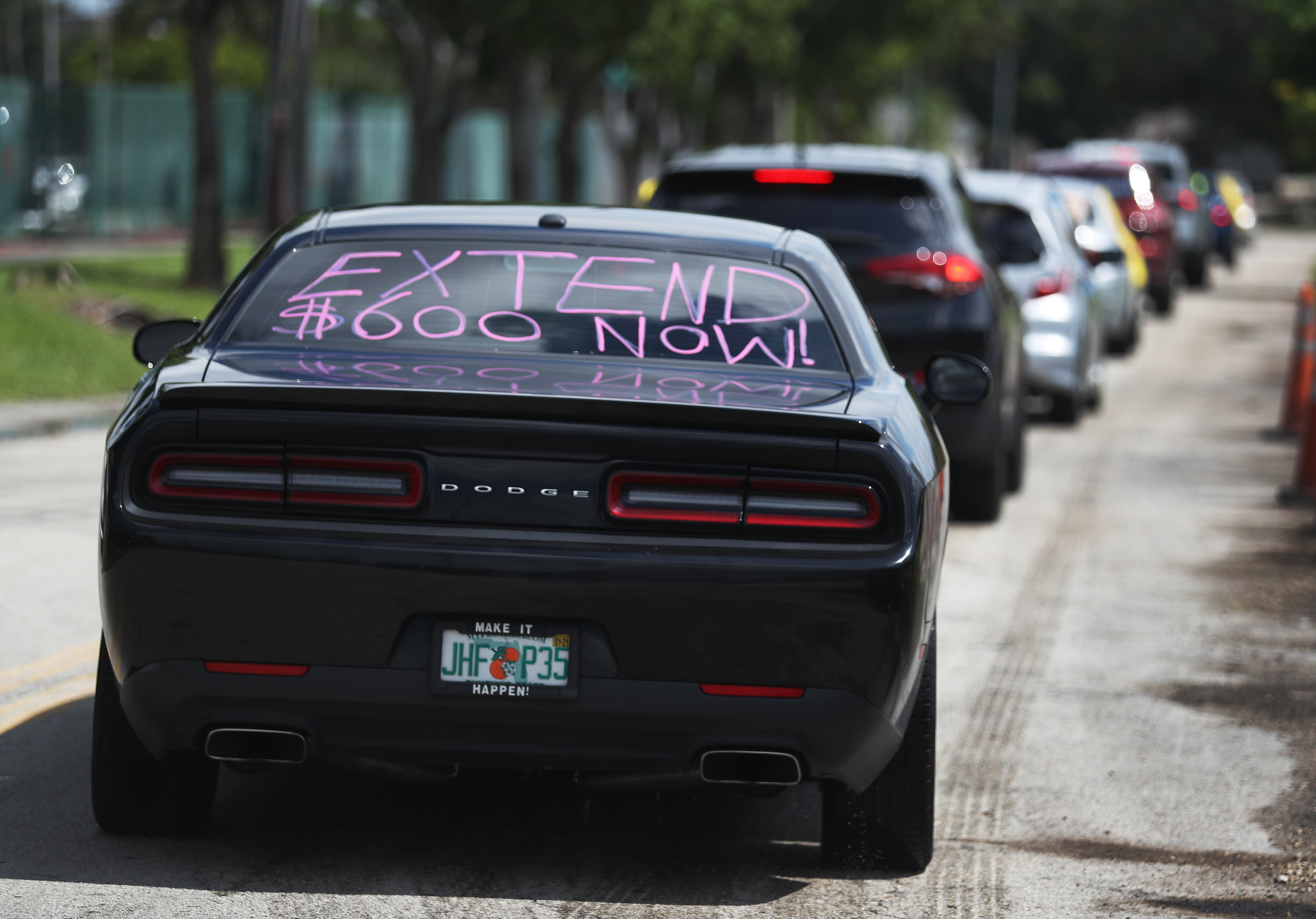 A car participates in a July 16, 2020 caravan protest headed for the Coral Gables, Florida, office of Sen. Rick Scott. Caravan participants asked Scott and other Senators to support extension of unemployment benefits for laid-off Americans.