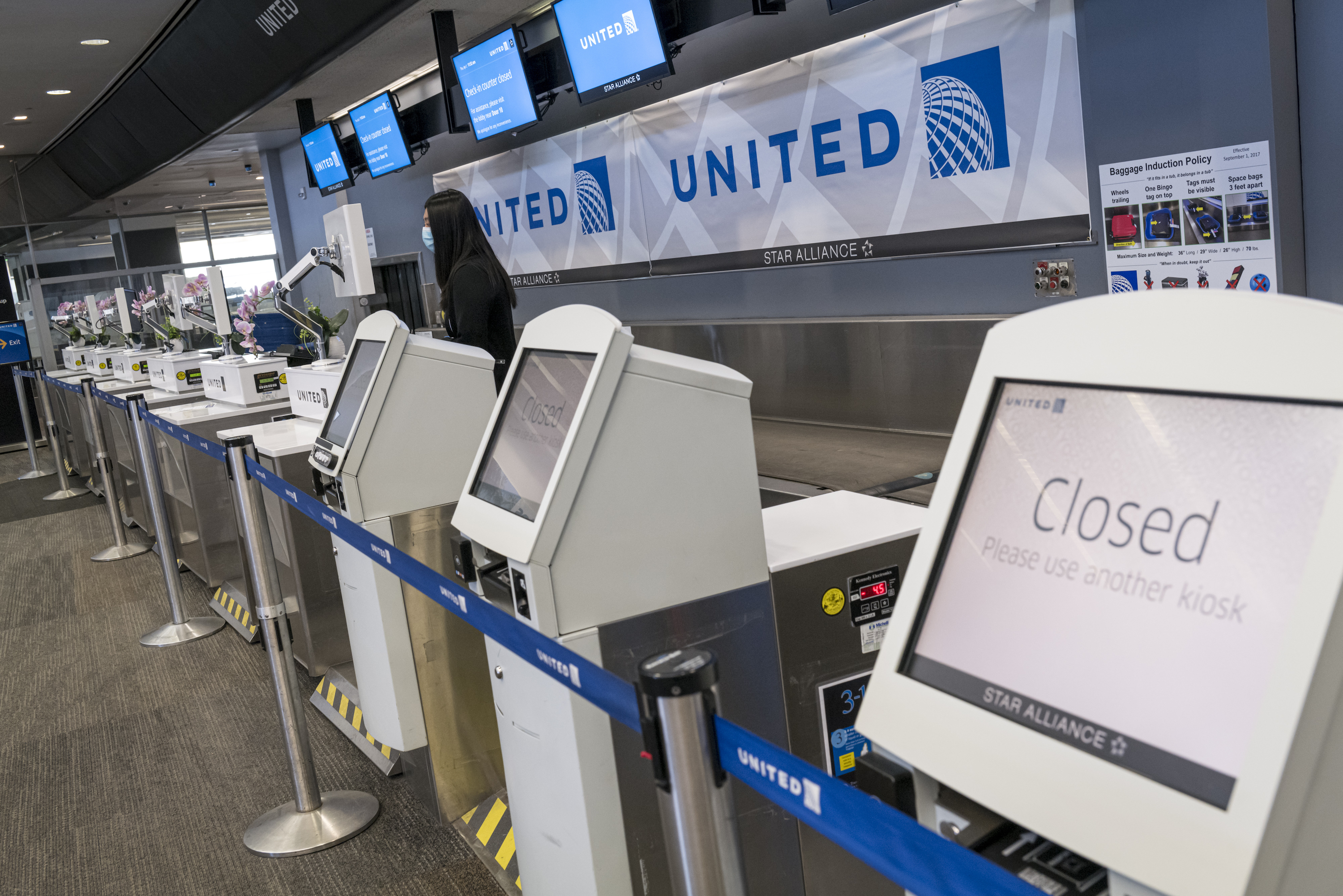 A United Airlines Holdings Inc. employee waits for a traveler at San Francisco International Airport in San Francisco, California, U.S., on April 2, 2020.