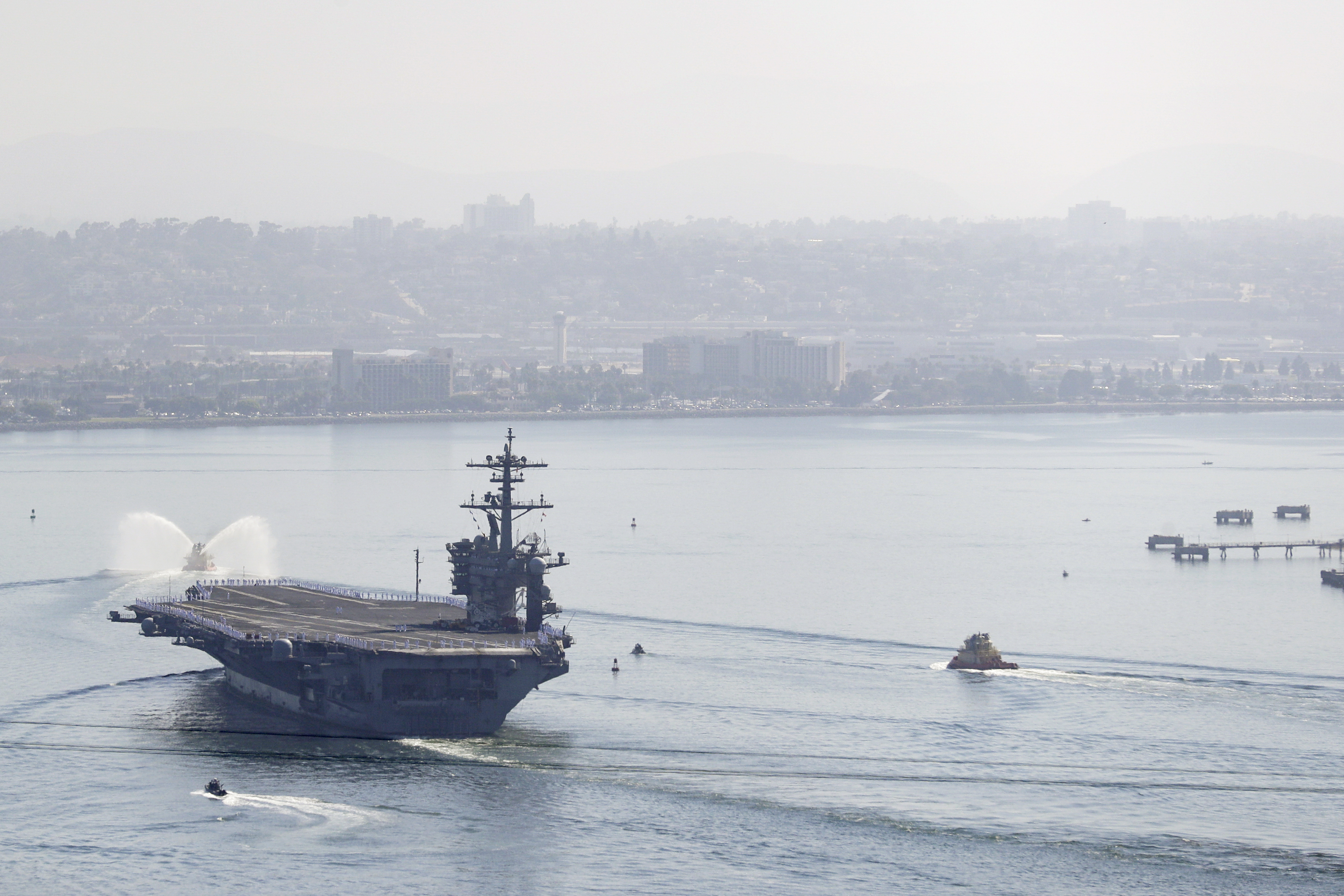 The U.S.S. Theodore Roosevelt aircraft carrier makes its way into San Diego Bay Thursday, July 9, 2020, seen from San Diego. The carrier returned home to San Diego Thursday, led by a new captain who came aboard after the previous commander was fired and the Navy secretary resigned over the handling of a massive COVID-19 outbreak on board.