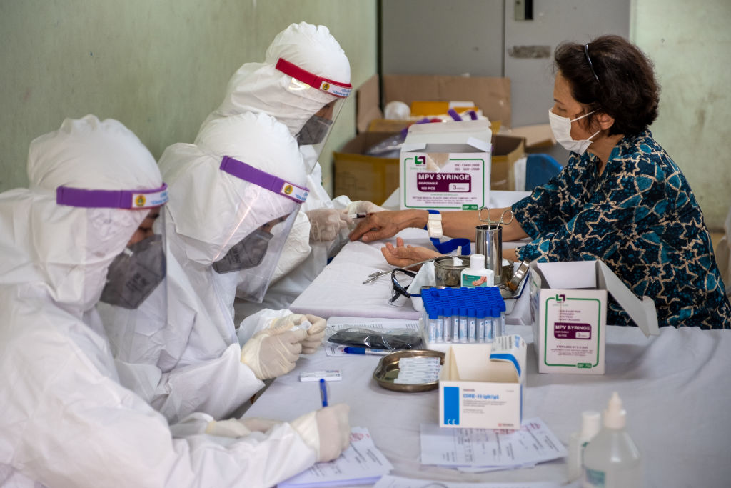 Medical specialists in protective suits collect blood samples for a coronavirus (COVID-19) rapid test from people who recently returned from Da Nang City on July 31, 2020 in Hanoi, Vietnam.