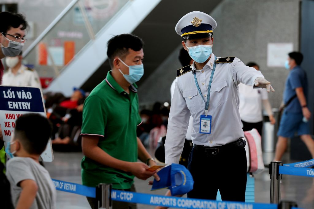 A staff member from Vietnam's Centre of Disease Control assists passengers wearing face masks as they queue up for temperature checks at the departures terminal at Danang's international airport on July 27, 2020.