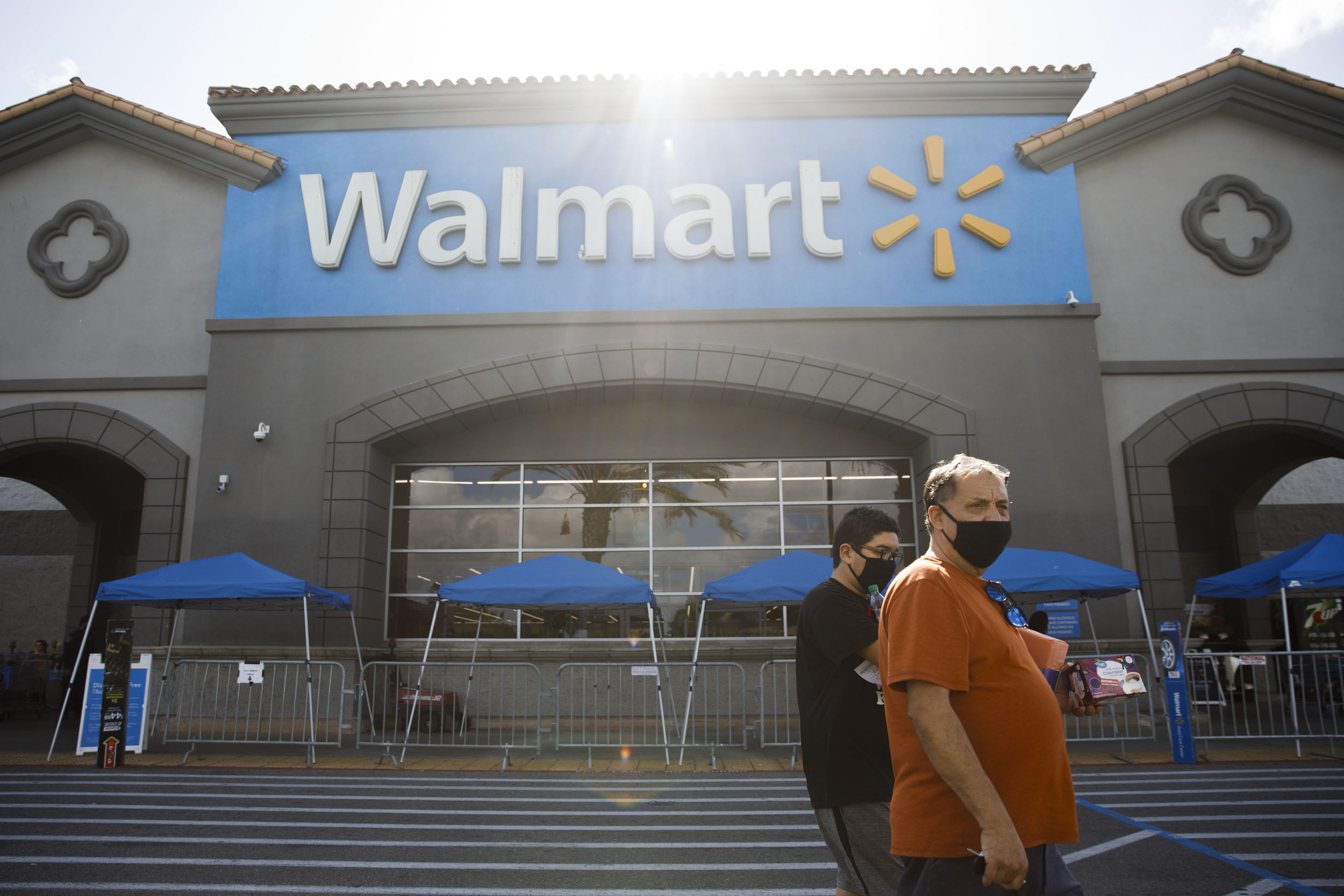Shoppers wearing protective masks walk outside a Walmart Inc. store in Torrance, California, U.S., on Tuesday, May 19, 2020.