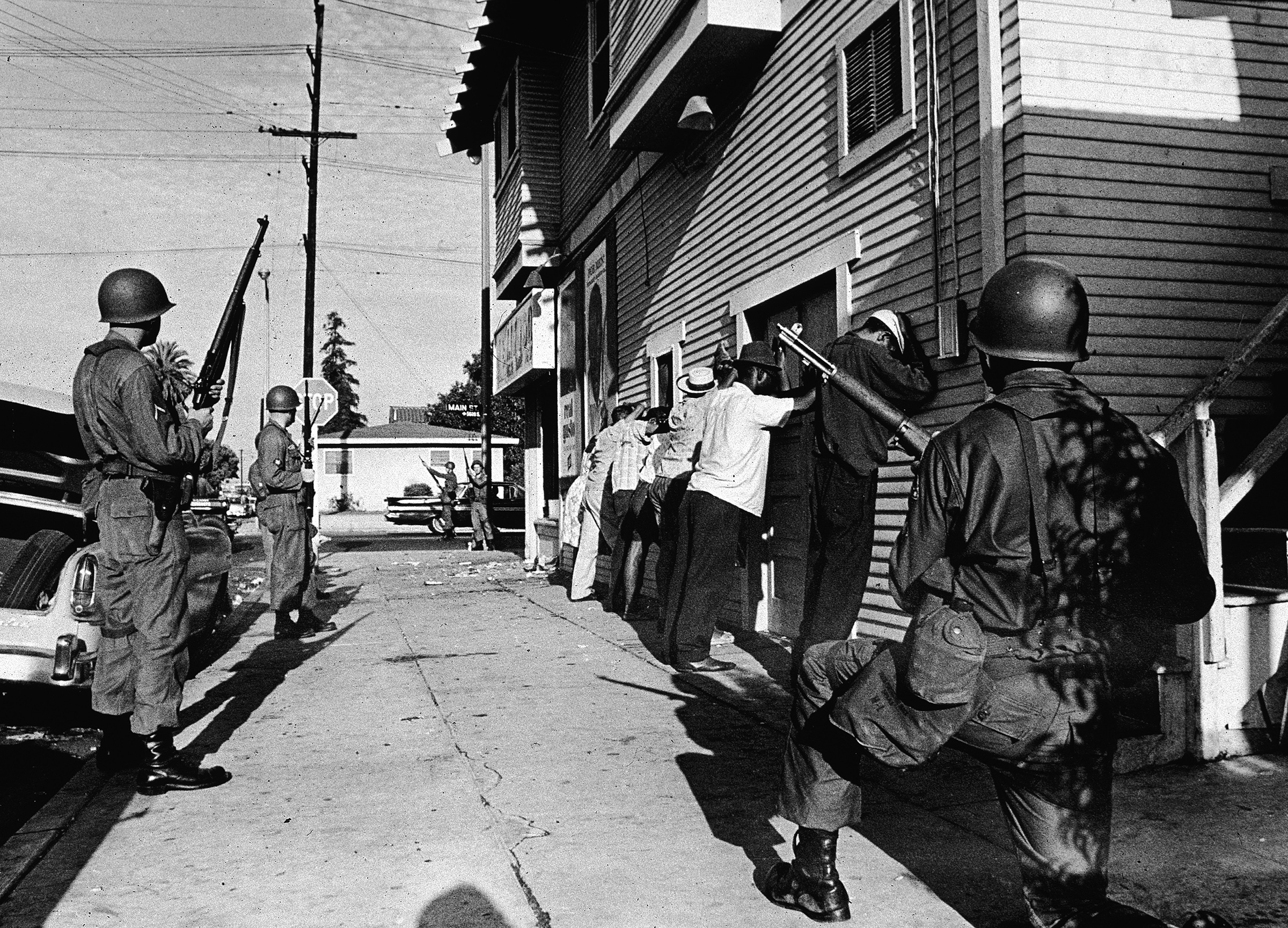 Armed National Guardsmen force a line of Black men to stand against the wall of a building during the Watts riots in 1965