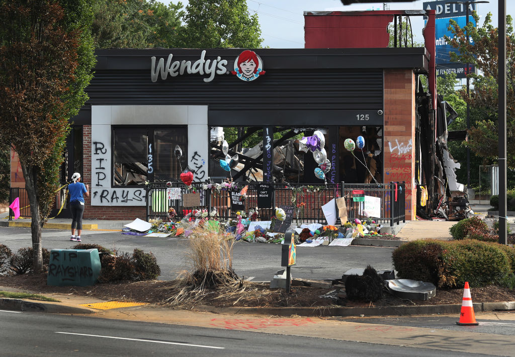 People visit the memorial setup outside the Wendy's restaurant on June 17, 2020 near where Rayshard Brooks was killed in Atlanta, Georgia.