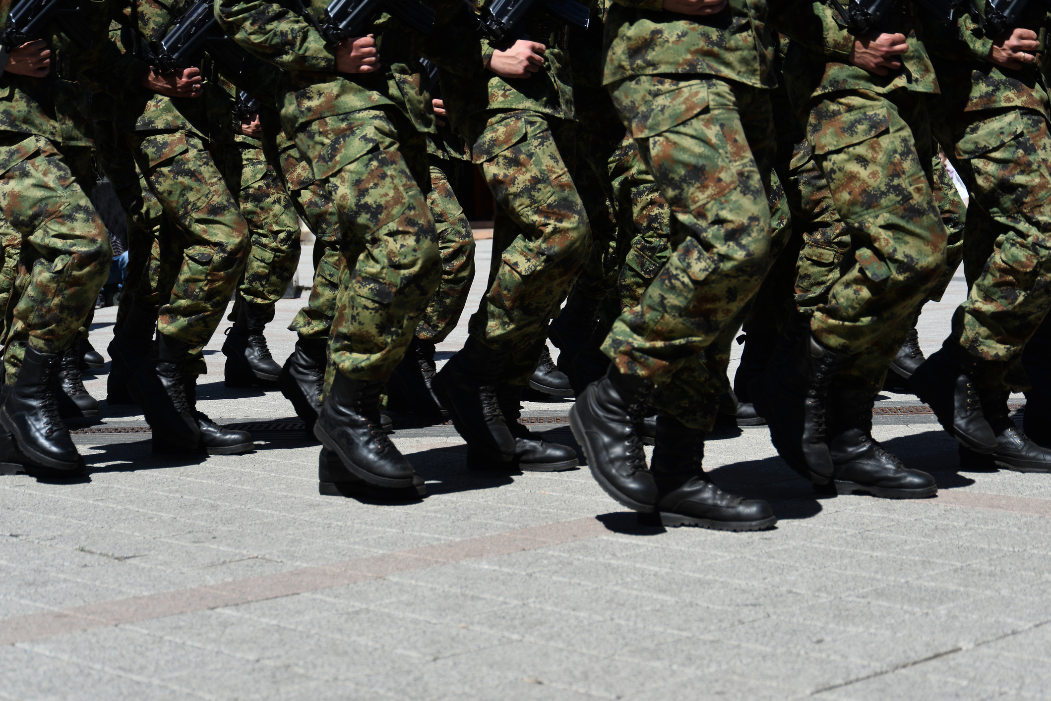 Army military soldiers marching in a parade outdoors.