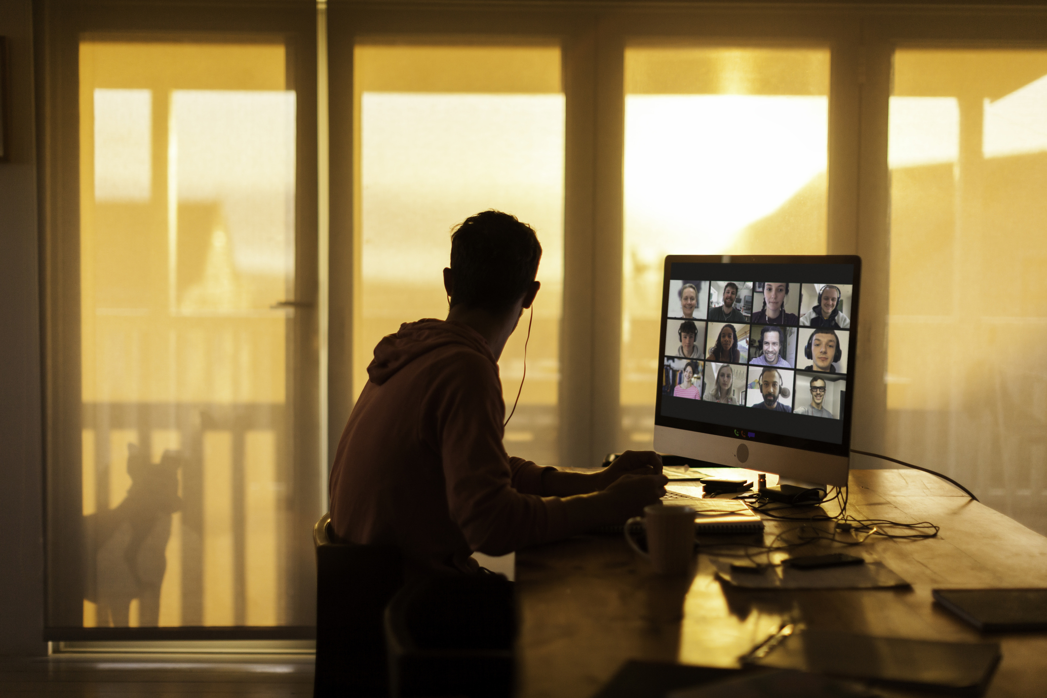 A young man participates in a video meeting.
