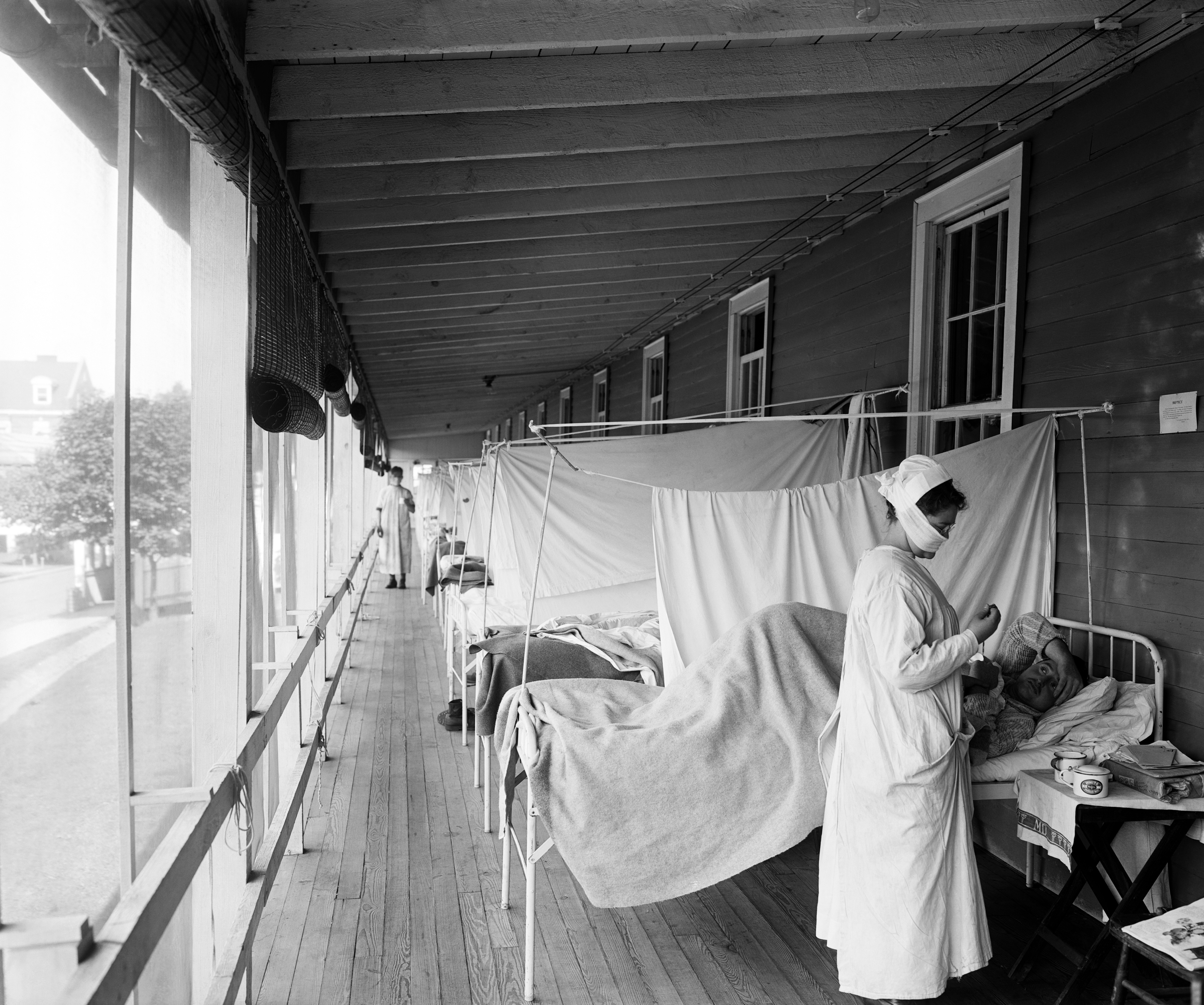 A nurse checking on a patient at the Walter Reed Hospital Flu Ward during the influenza pandemic, Washington, D.C., circa 1918.
