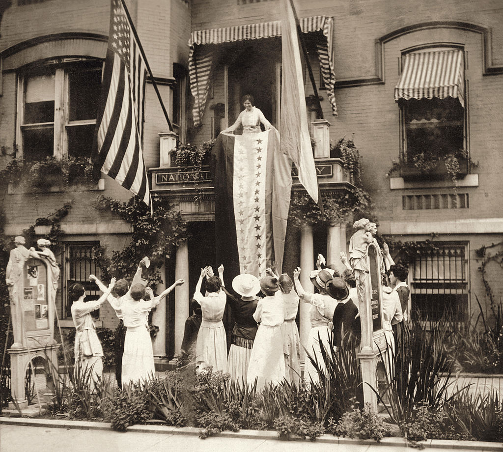 An August 1920 photo of American suffragist Alice Paul standing on a balcony at the National Women's Party headquarters in Washington, D.C., and unfurling a banner in celebration of the state of Tennessee's ratification of the 19th Amendment.