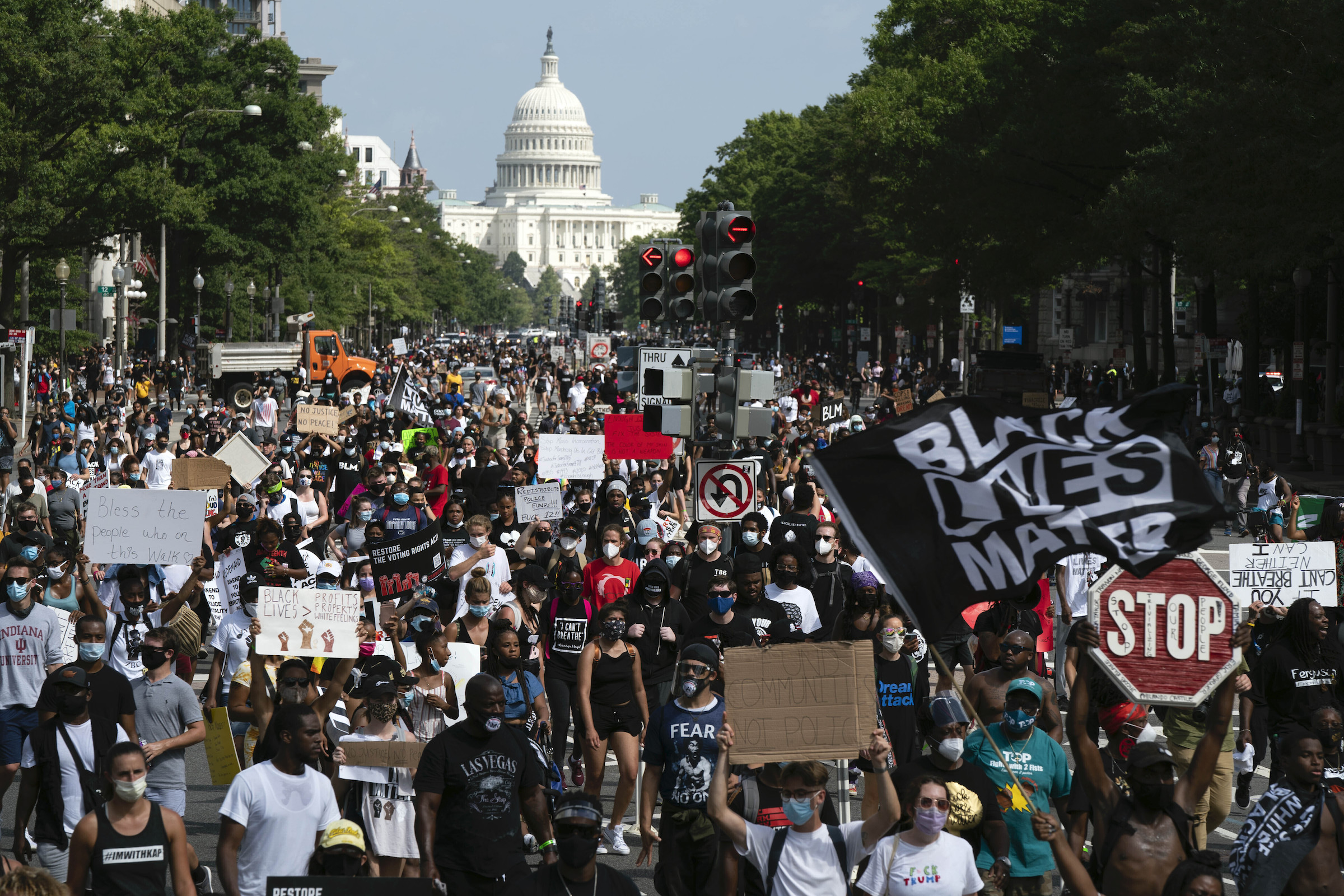 People walk on Pennsylvania Avenue during the March on Washington, Friday Aug. 28, 2020, on the 57th anniversary of the Rev. Martin Luther King Jr.'s  I Have A Dream  speech.