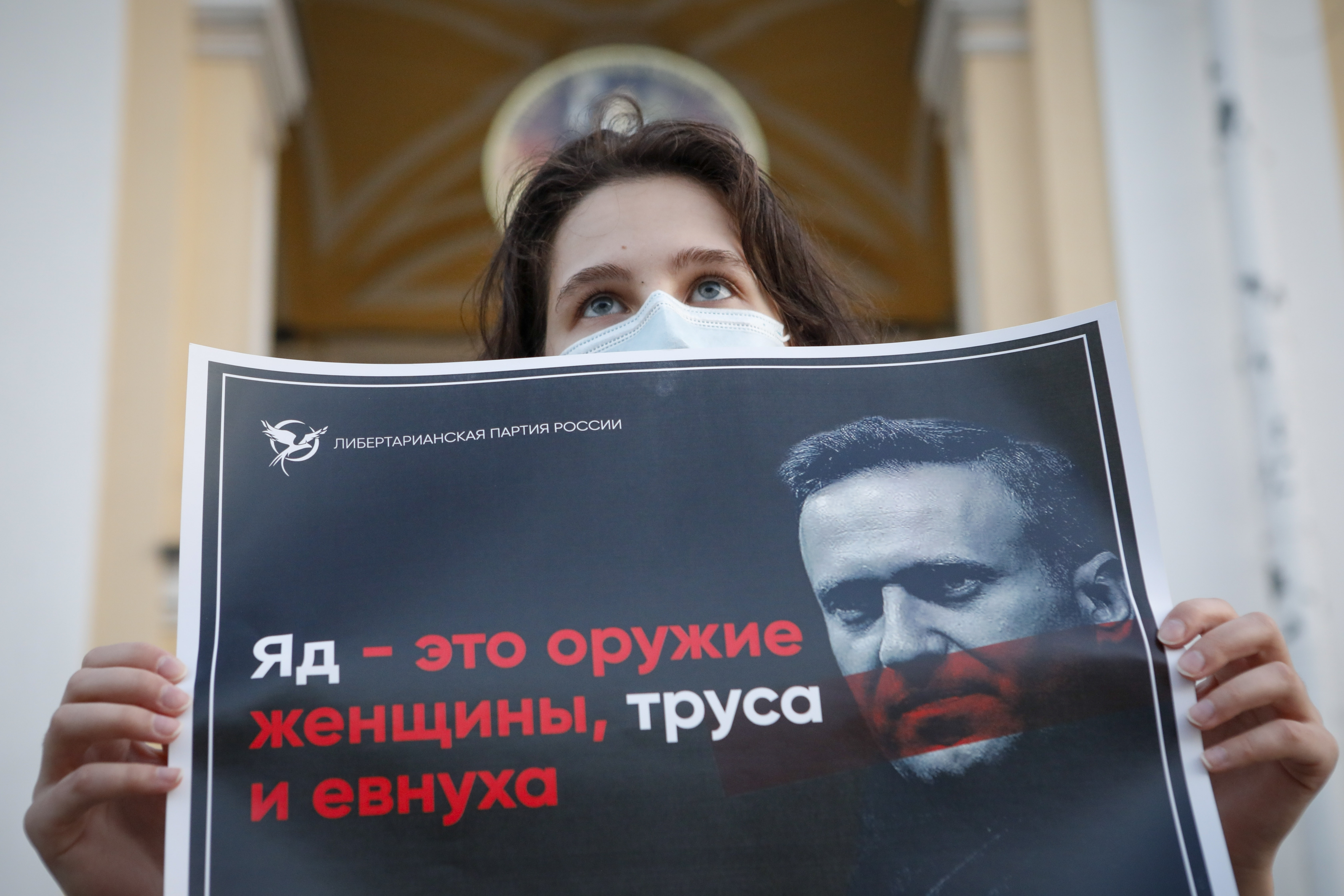 A protester holds a poster reading  poison is the weapon of a woman, a coward and a eunuch!  during a picket in support of Russian opposition leader Alexei Navalny in the center of St. Petersburg, Russia, Thursday, Aug. 20, 2020.