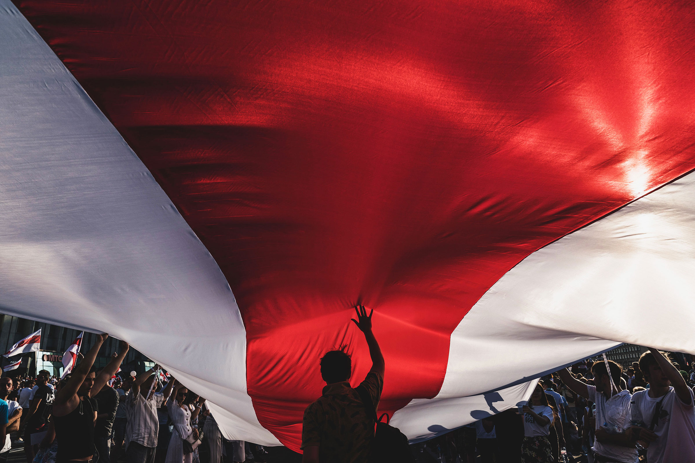 Protesters unfurl a banner in the colors of the former Belarus national flag as they call for the resignation of President Alexander Lukashenko in Minsk, Belarus, on, Aug. 16, 2020.