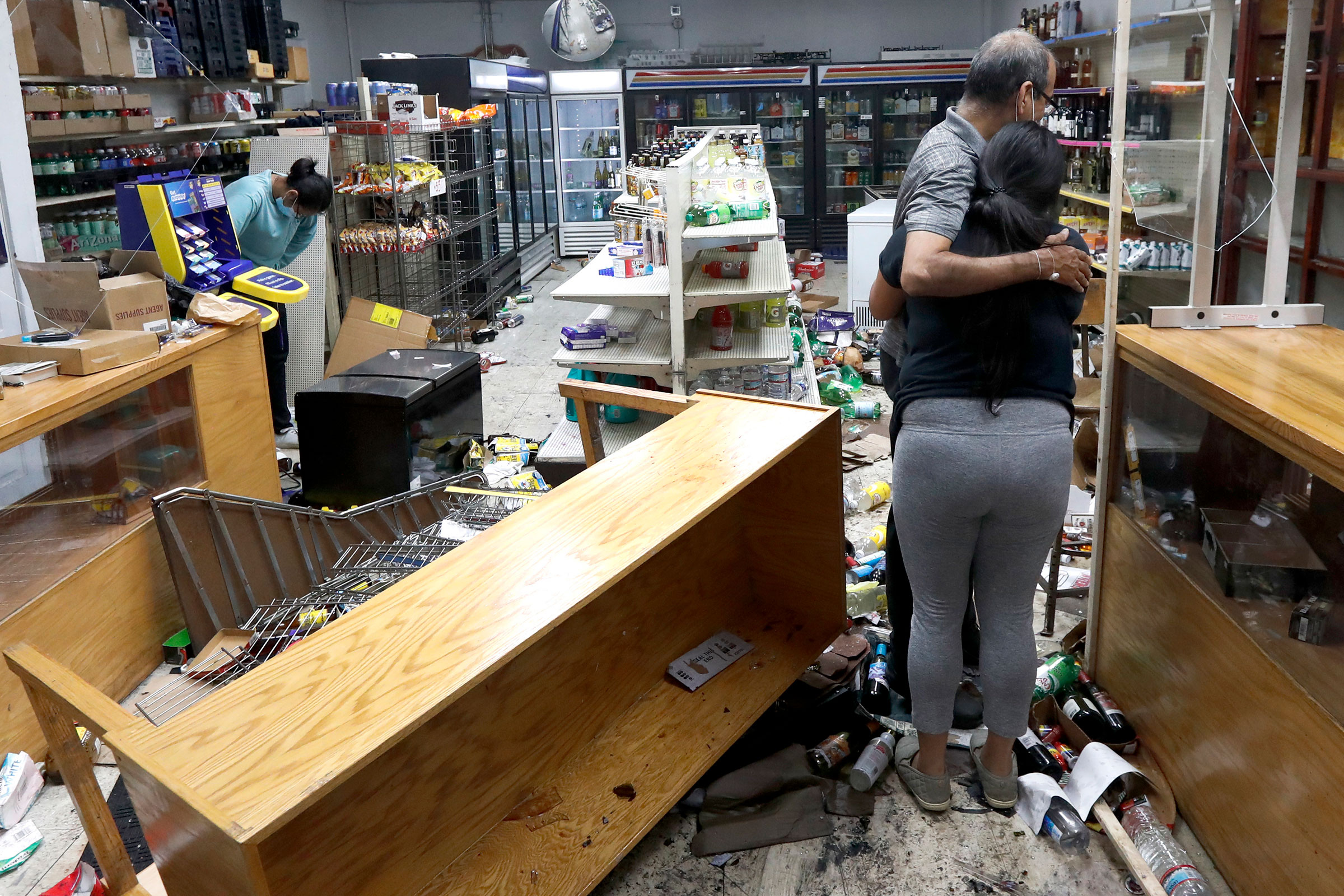 Yogi Dalal hugs his daughter Jigisha as his other daughter Kajal, left, bows her head at the family food and liquor store on, Aug. 10, 2020, after the family business was vandalized in Chicago.