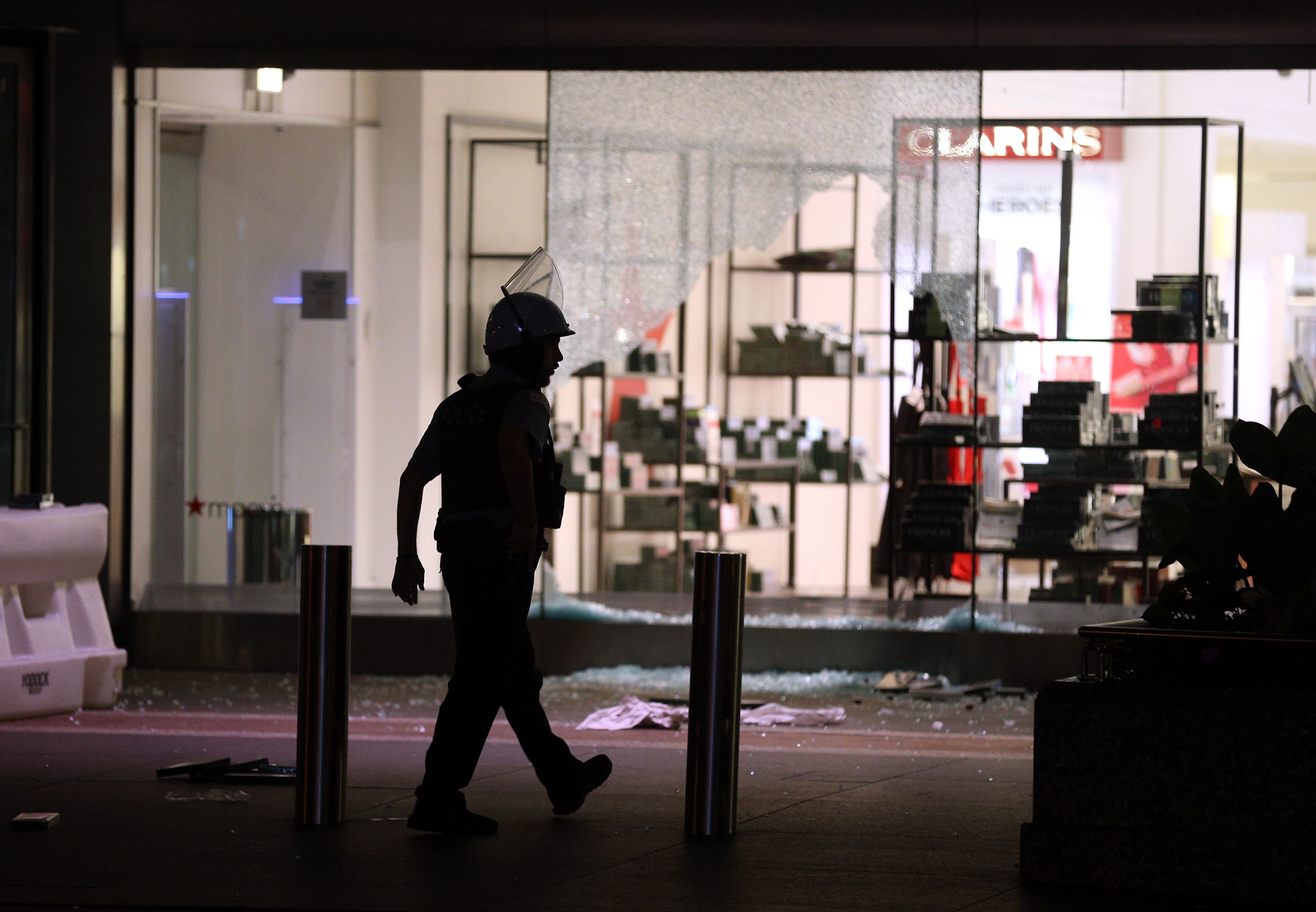 A Chicago Police officer walks past Macy's on North Michigan Avenue in Chicago after the store and others in the area were looted early Monday Aug. 10, 2020.