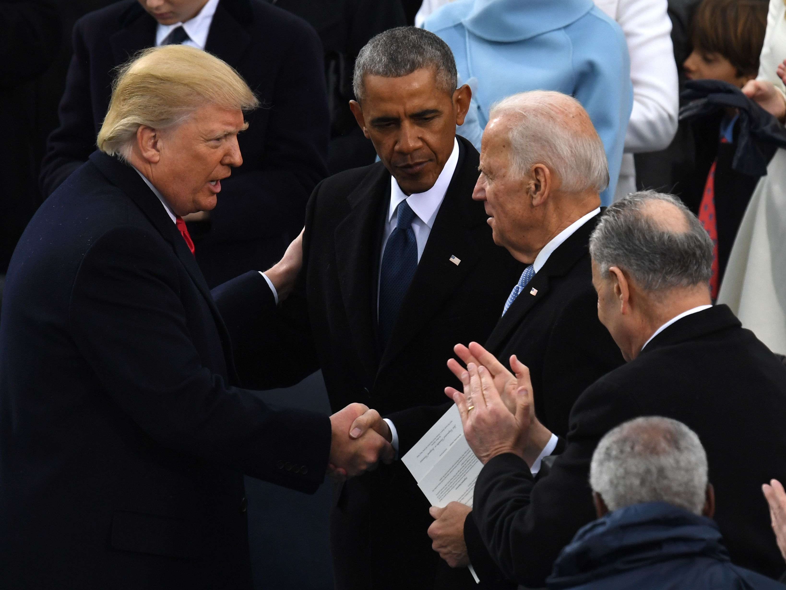 U.S. President Donald Trump shakes hands with former U.S. President Barack Obama and former Vice President Joe Biden after being sworn in as President on January 20, 2017 at the U.S. Capitol in Washington, DC.