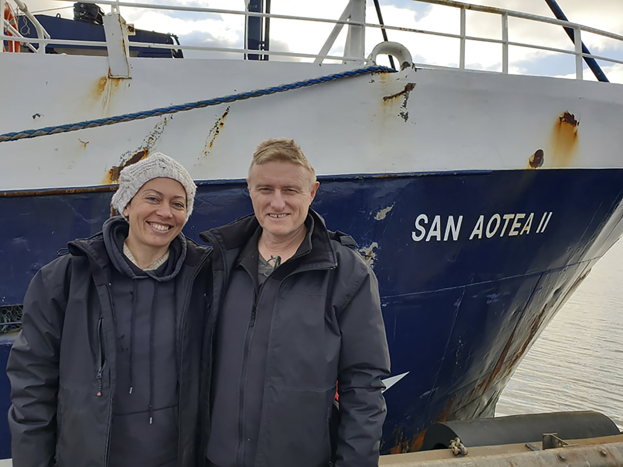In this July 2020, photo supplied by Feeonaa and Neville Clifton, Neville and Feeonaa Clifton are pictured by the San Aotea II fishing boat in the Falkland Islands. The Cliftons, a honeymoon couple who were stranded on the remote Falkland Islands in March because of the coronavirus have managed to get home to New Zealand, Tuesday Aug. 4, 2020 by hitching a lift of more than 5,000 nautical miles (9,200 kilometers) on an Antarctic fishing boat.