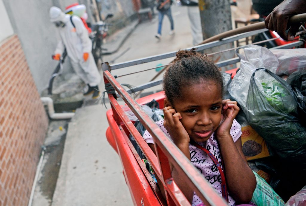 A girl covers her ears as people disinfect an area at the Babilonia favela, in Rio de Janeiro on April 18, 2020.