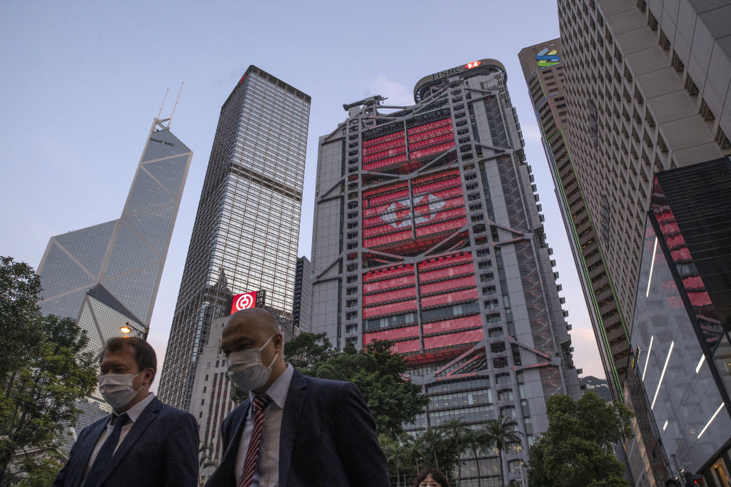 Pedestrians wearing protective masks walk as the HSBC Holdings Plc headquarters building, center, stands illuminated in the Central district of Hong Kong, China, on Monday, April 27, 2020.