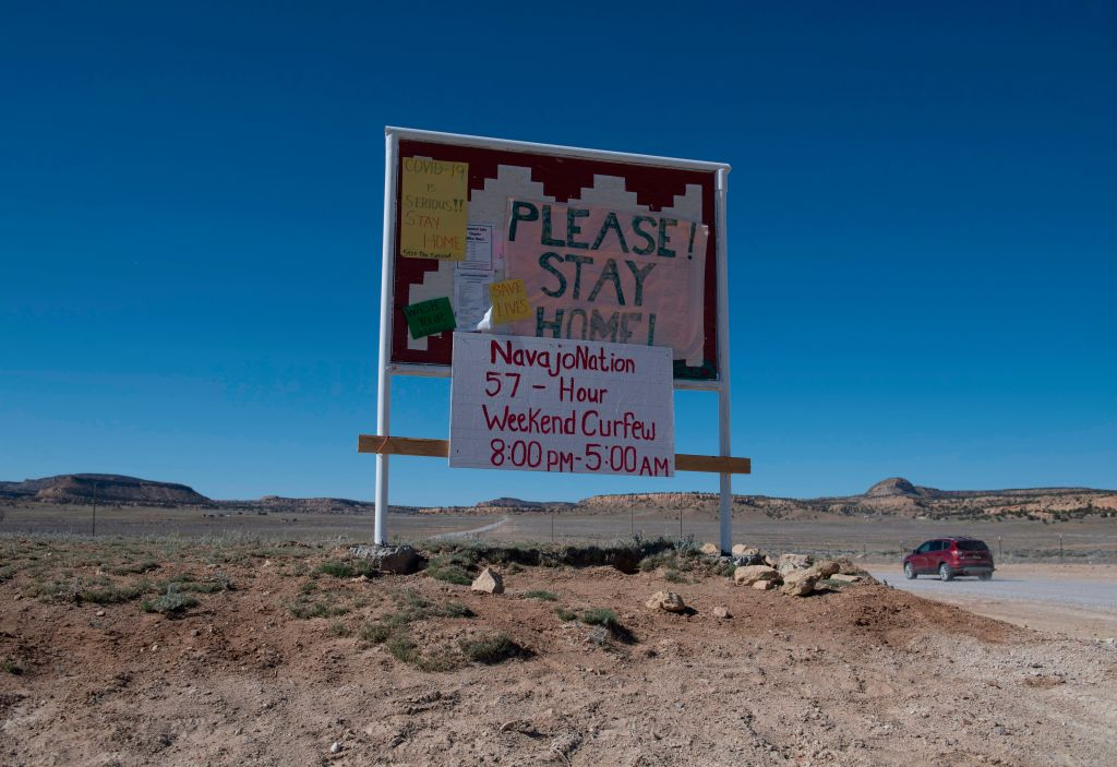 A sign warning of the Covid-19 virus as Navajo Indians prepare to line up in their vehicles to collect water and supplies from a distribution point, as the Covid-19 virus spreads through the Navajo Nation, in the town of Casamero Lake in New Mexico, May 20, 2020.