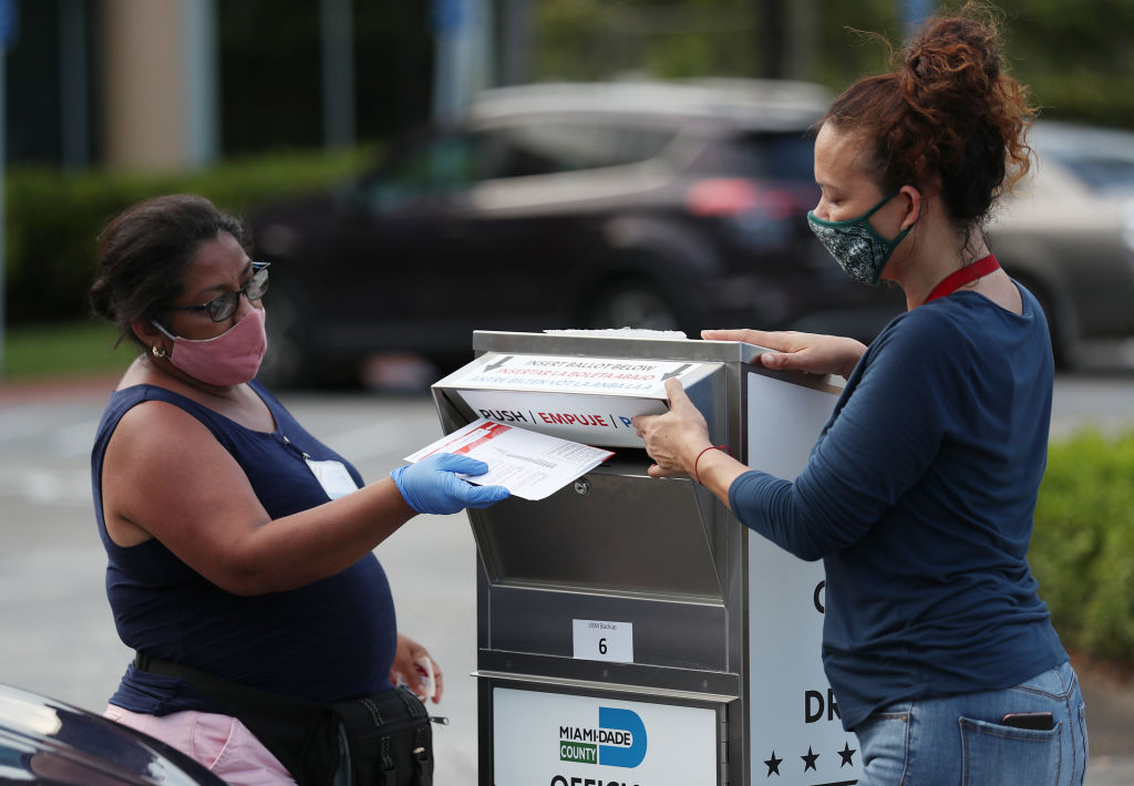 Poll workers at the Miami-Dade County Elections Department deposit peoples' mail in ballots into an official ballot drop box on primary election day on August 18.