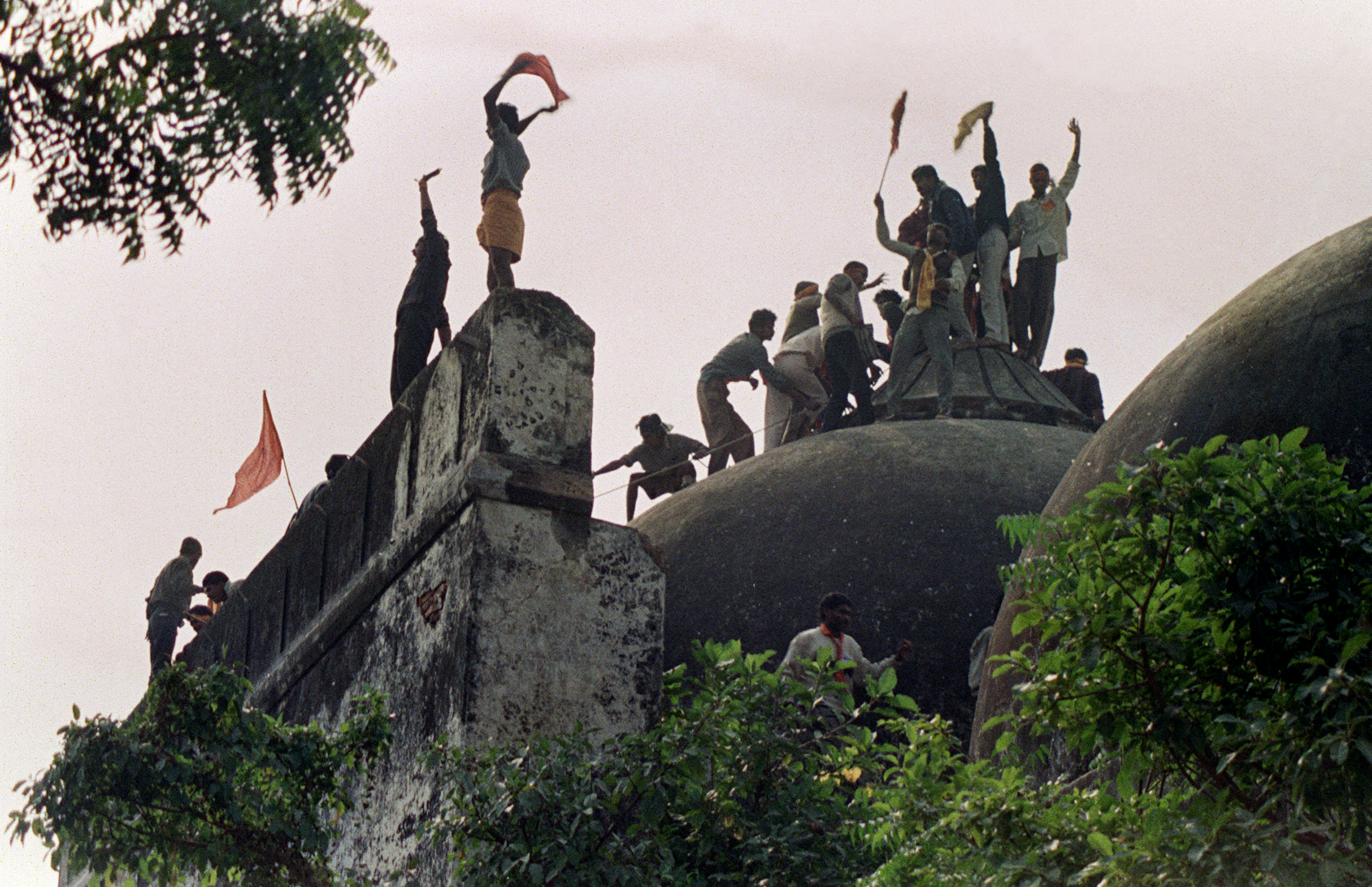 December 6, 1992: Hindu mob climb atop the 16th century Muslim Babri Mosque five hours before the structure was completely demolished by hundreds supporting Hindu fundamentalist activists.