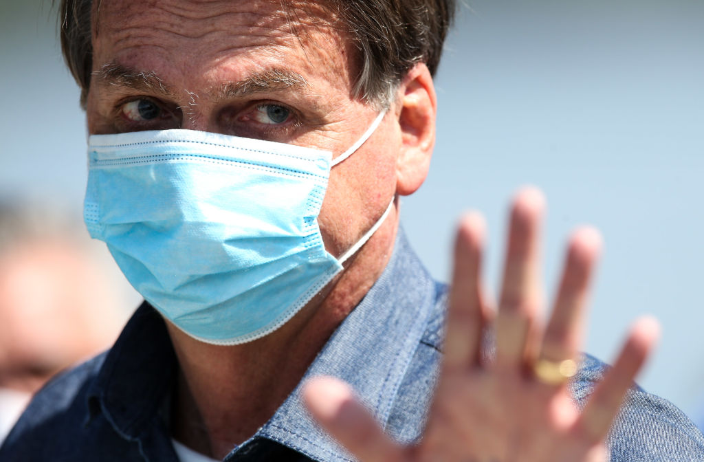 President of Brazil Jair Bolsonaro waves during a visit to Barreiros bridge amidst the coronavirus pandemic on August 7, 2020 in Sao Vicente, Brazil.