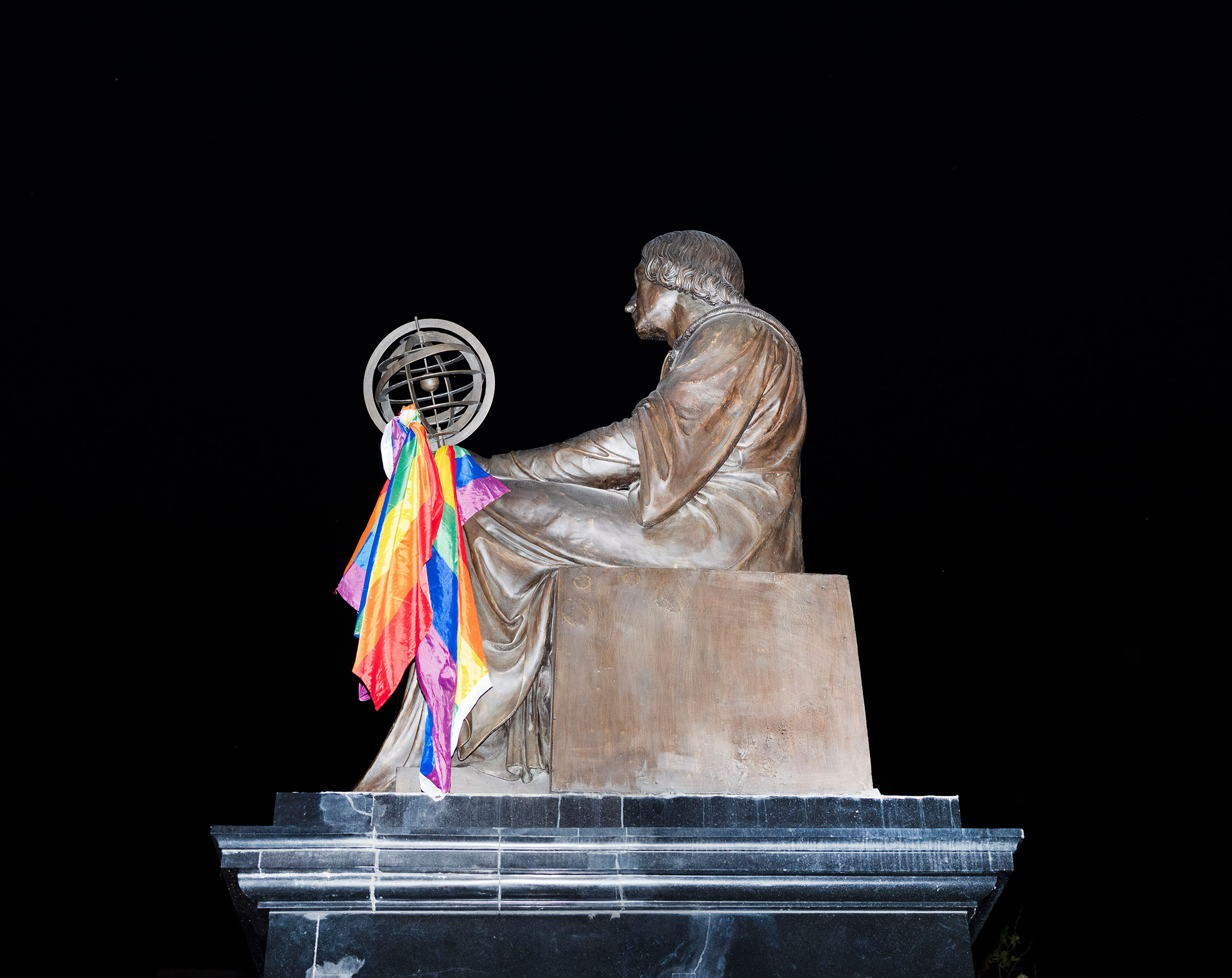 The Nicolaus Copernicus monument is decorated with a rainbow flag.