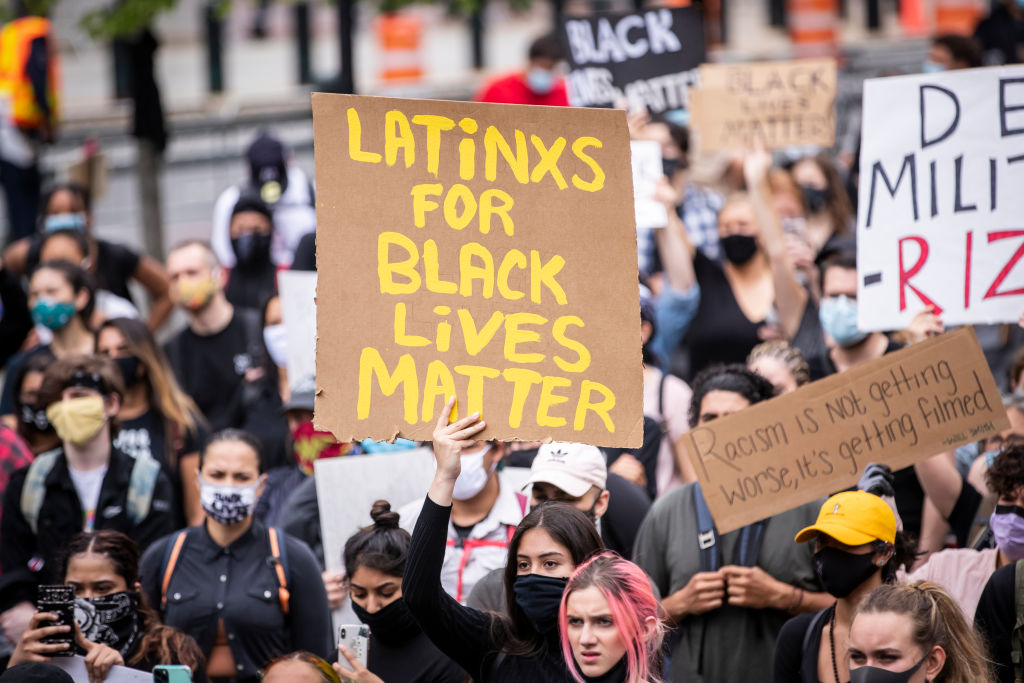 A  protester holds a sign that says,  Latinxs For Black Lives Matter  among the large crowd in Foley Square in New York City on June 02, 2020.