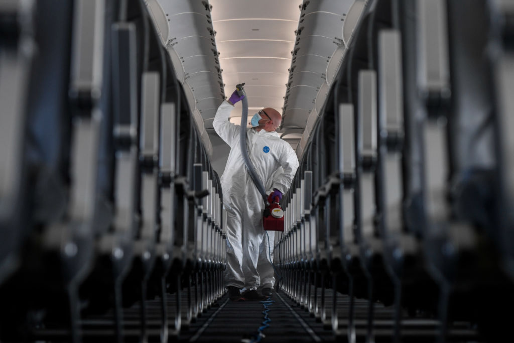 Brandon Wilson, owner of AvidJet, disinfects a Frontier airplane with a fogger at Denver International Airport on Tuesday, May 6, 2020.