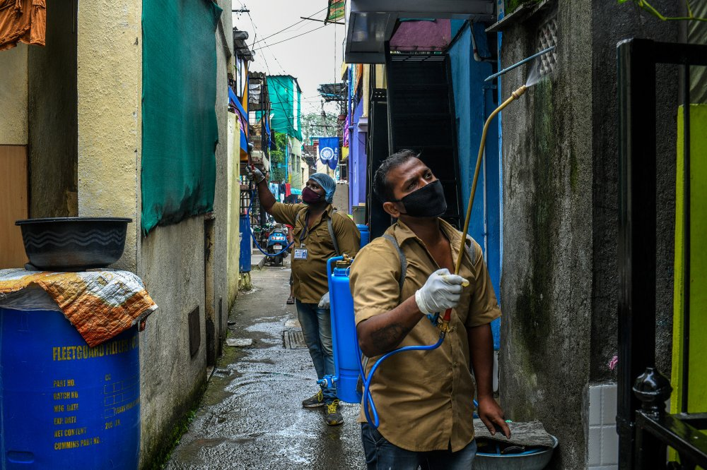 Workers from the Pune Municipal Corporation spray disinfectant in the Tadiwala Chawl area.