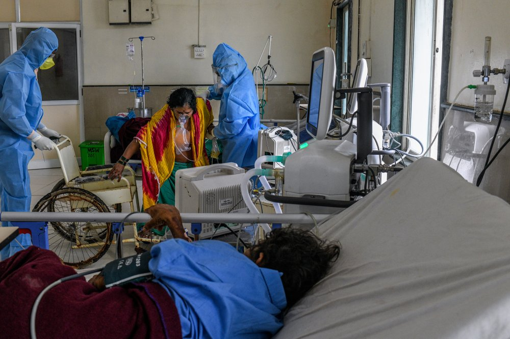 After her condition improved, a COVID-19 patient is helped into a wheelchair so she can be transferred from the intensive-care unit to an observation ward.