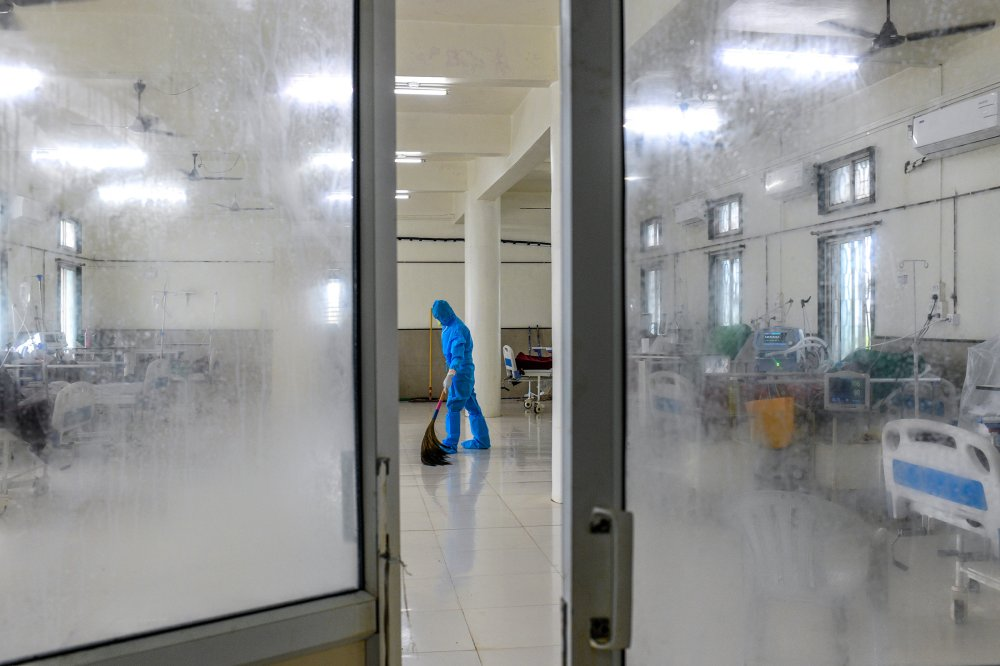 A young worker dressed in personal protective equipment sweeps the floor of the intensive-care unit.