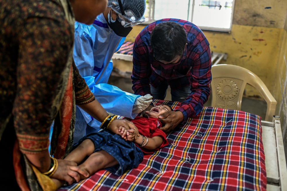 Parents keep their child still while a health care worker takes a nasal swab for a COVID-19 test at a school in Pune.