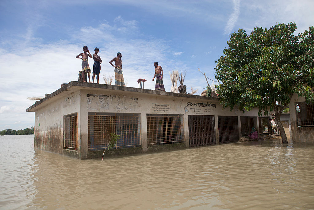 People take shelter on the roof of a school in Jamalpur, Bangladesh in 2016. Around 1.5 million people were affected by flooding that summer, according to the Bangladesh Disaster Management Bureau. In 2020, a third of the country has been hit with dramatic flooding.