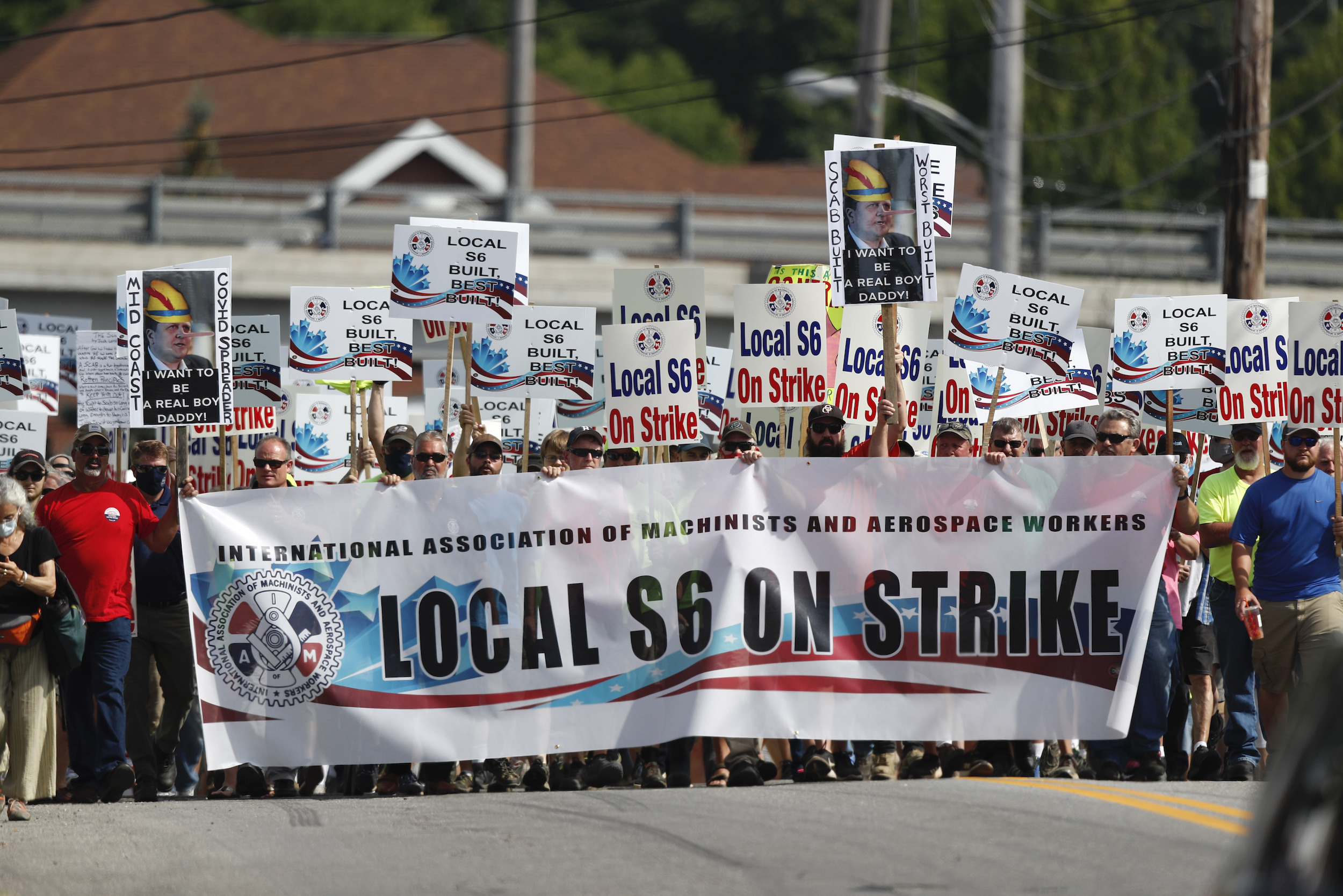 Striking Bath Iron Works shipbuilders march in solidarity on July 25, 2020, in Bath, Maine.