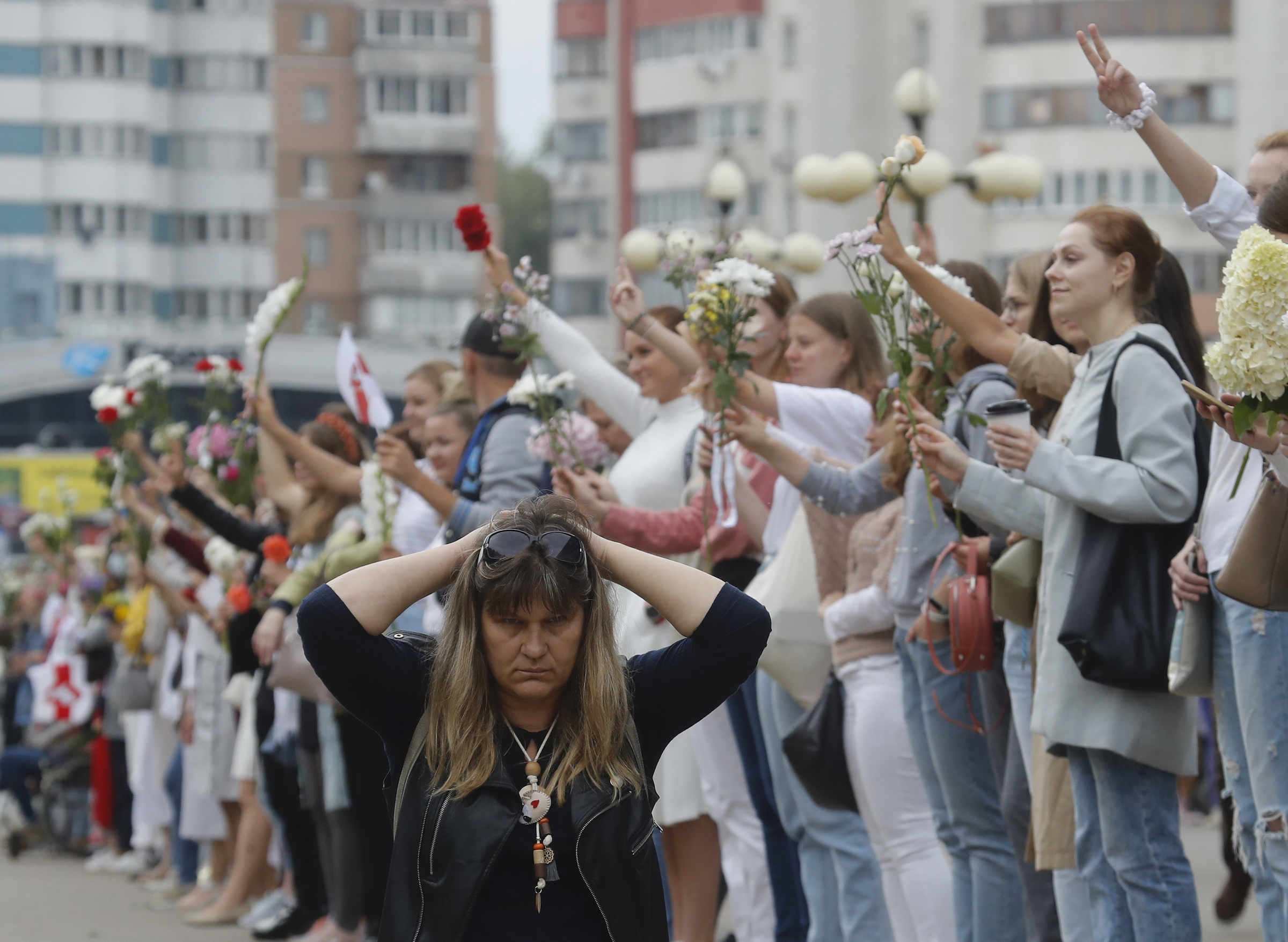 A woman kneels on the ground as people create a human chain during a protest in Minsk, Belarus, on Aug. 22, 2020.