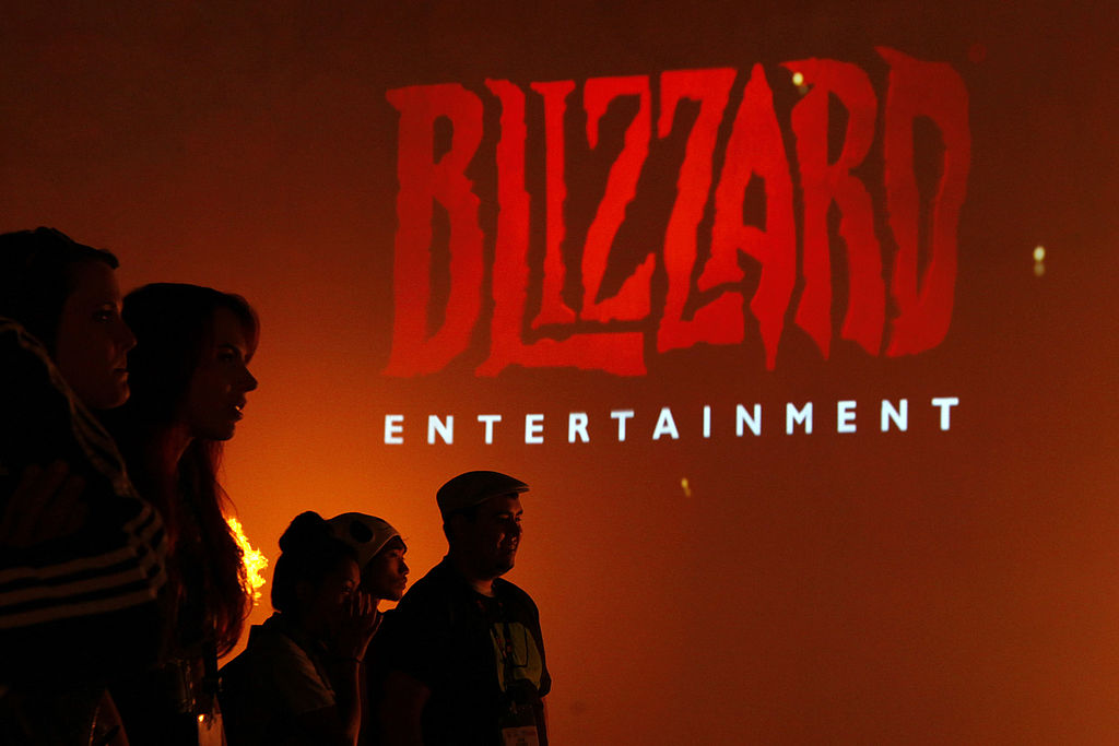 Attendees stand in front of the logo for Blizzard Entertainment Inc., a unit of Activision Blizzard Inc., as they watch a trailer for the company's Diablo III video game during the E3 Electronic Entertainment Expo in Los Angeles, California, U.S., on Wednesday, June 12, 2013. E3, a trade show for computer and video games, draws professionals to experience the future of interactive entertainment as well as to see new technologies and never-before-seen products.