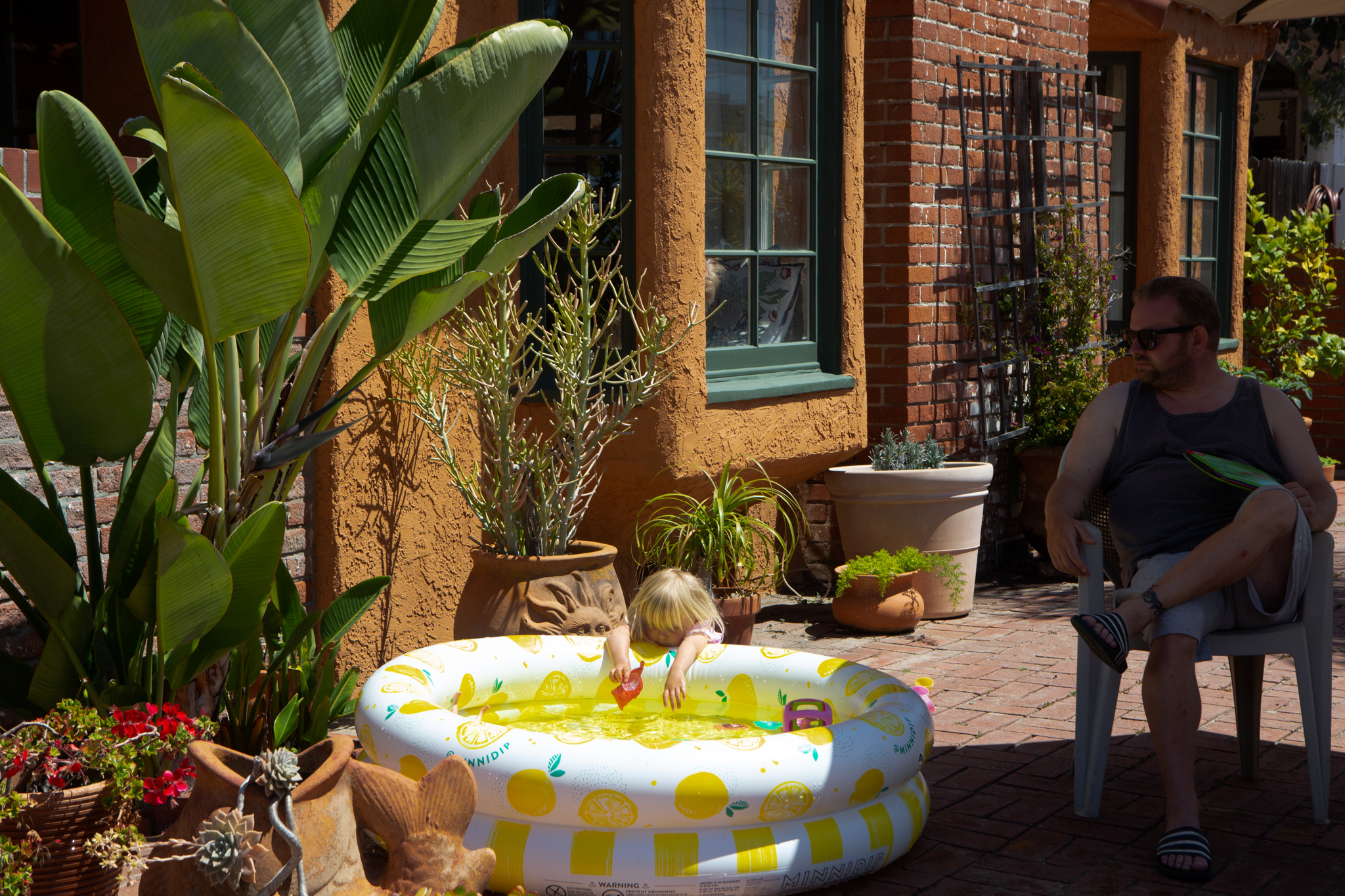 Bowie Davis, 3, plays in her kiddie pool while her father, Ed Davis, watches at their home during a heatwave on April 25, 2020 in Hermosa Beach, Calif.
