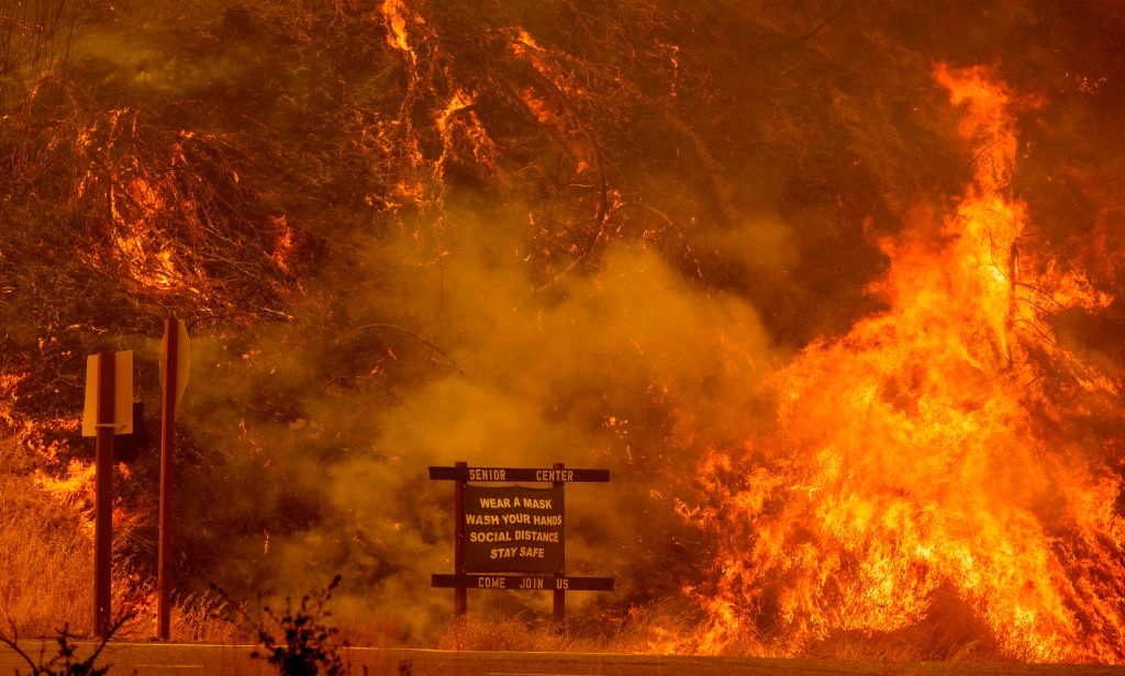 A sign warning people about COVID-19 is surrounded by flames during the Hennessey fire on Aug. 18, 2020, near Lake Berryessa in Napa, Calif.