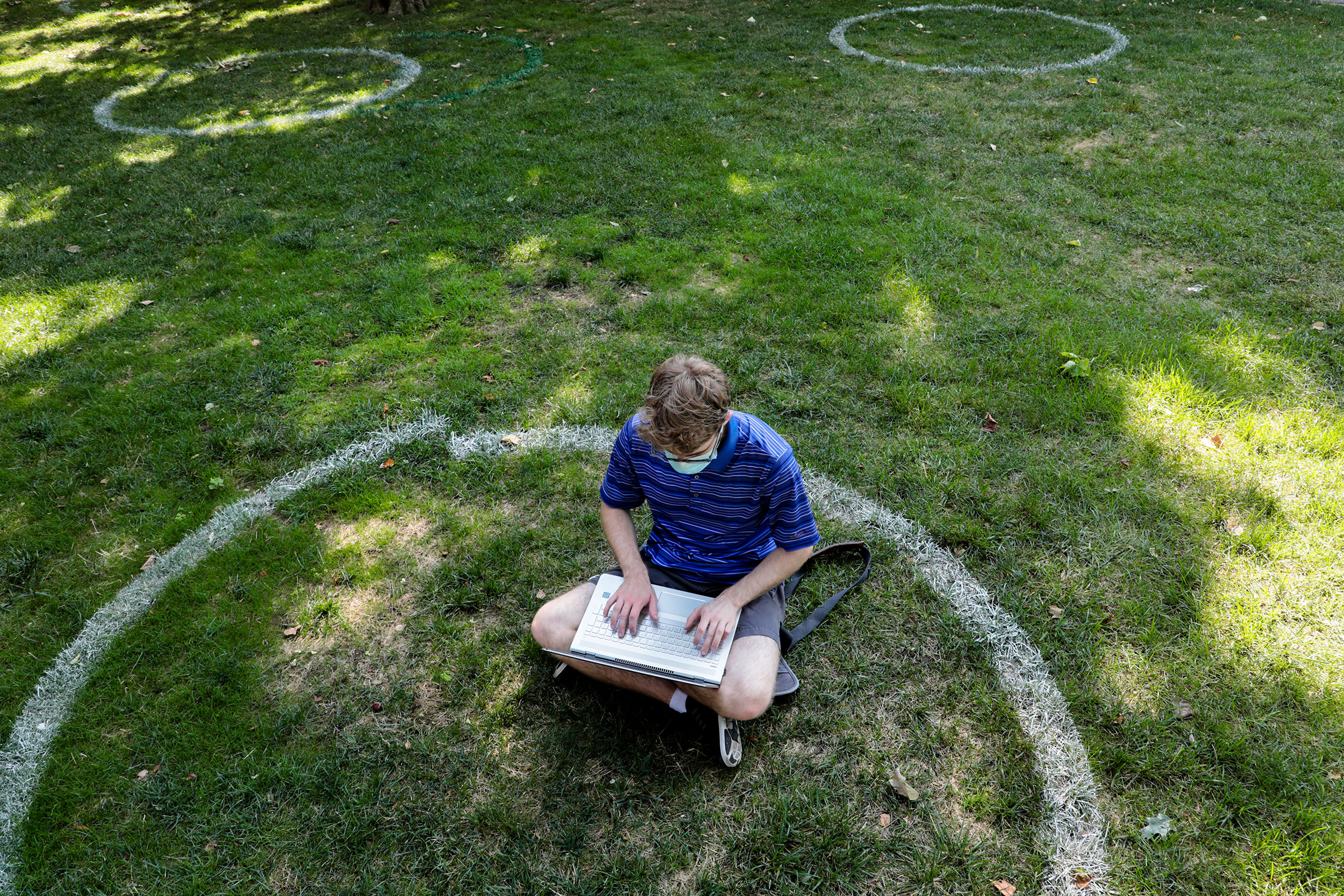 Logan Armstrong, a Cincinnati junior, works while sitting inside a painted circle on the lawn of the Oval during the first day of fall classes on at Ohio State University on Aug. 25, 2020.
