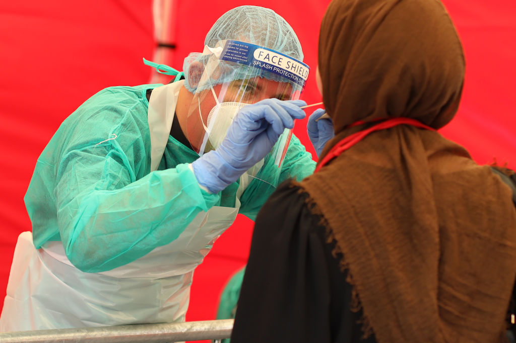 An employee takes a throat swab sample from a woman seeking a test for possible COVID-19 infection at a test station in Bonn, Germany on Aug. 24, 2020.