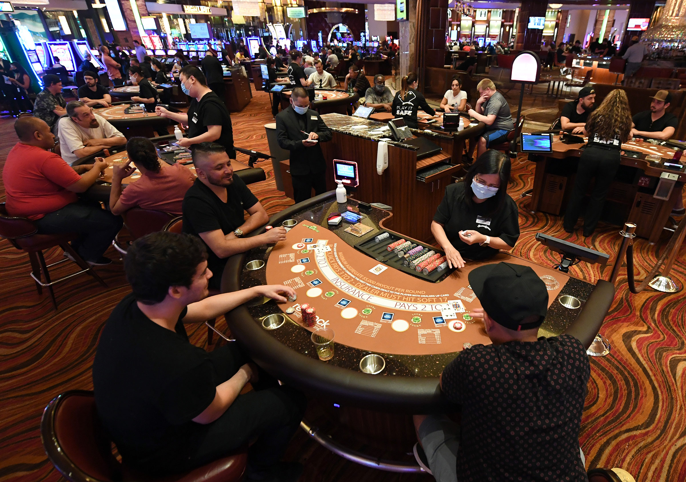 Guests play blackjack at tables with only three players allowed at a time at the Red Rock Resort after the property opened for the first time since being closed on March 17 because of the coronavirus pandemic on June 4, 2020 in Las Vegas, Nevada.