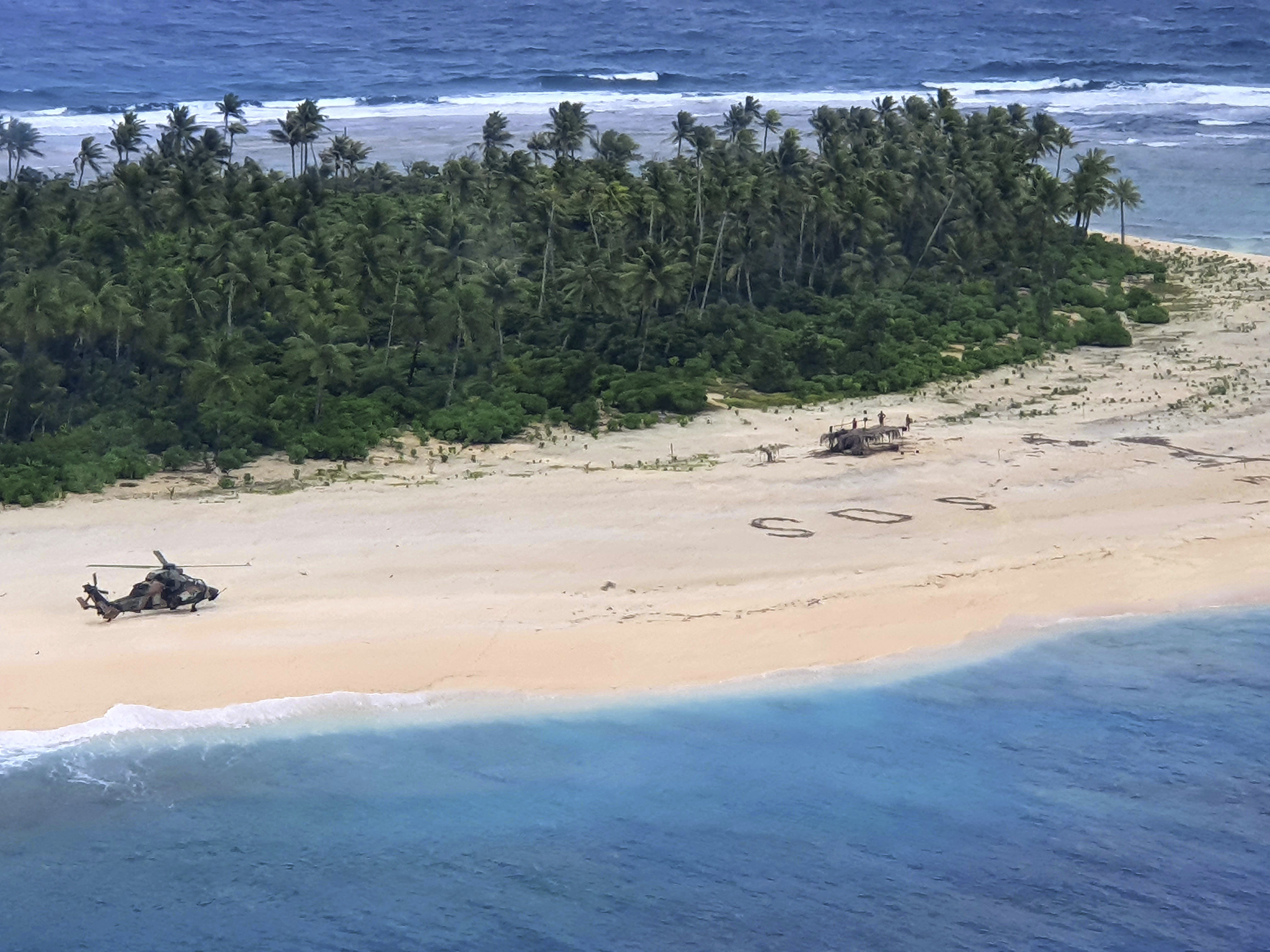 In this photo provided by the Australian Defence Force, an Australian Army helicopter lands on Pikelot Island in the Federated States of Micronesia, where three men were found, Sunday, Aug. 2, 2020, safe and healthy after missing for three days. The men were missing in the Micronesia archipelago east of the Philippines for nearly three days when their  SOS  sign was spotted by searchers on Australian and U.S. aircraft, the Australian defense department said.