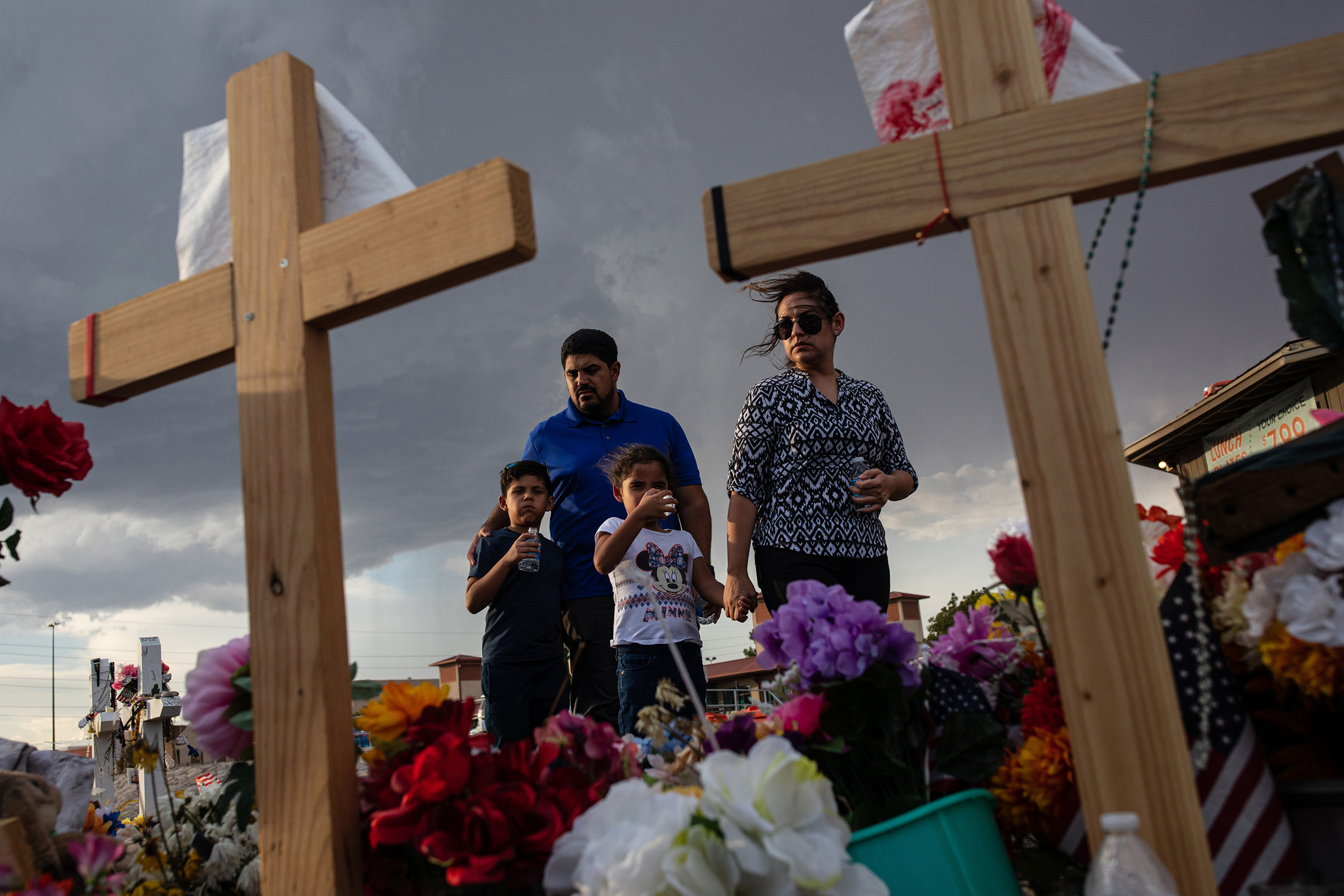 The Valenzuela family visits a makeshift memorial for victims of the shooting that killed 22 people at a Walmart store, in El Paso, Texas, on Aug. 27, 2019.