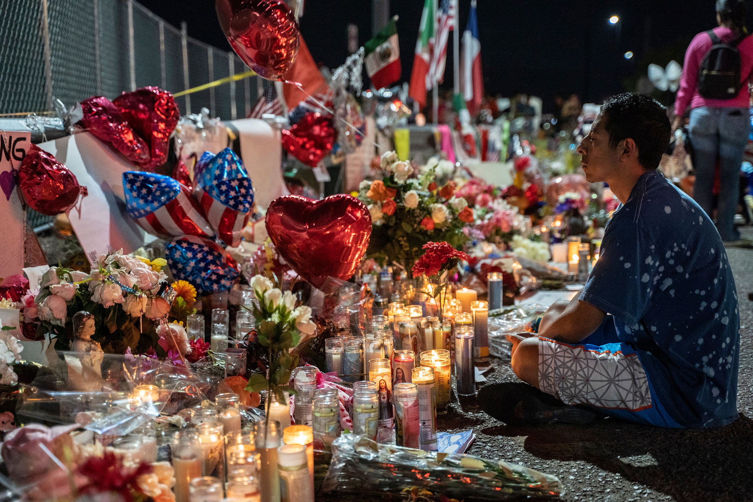 Abel Valenzuela meditates in front of the makeshift memorial for shooting victims at the Cielo Vista Mall Walmart in El Paso, Texas on August 8, 2019.