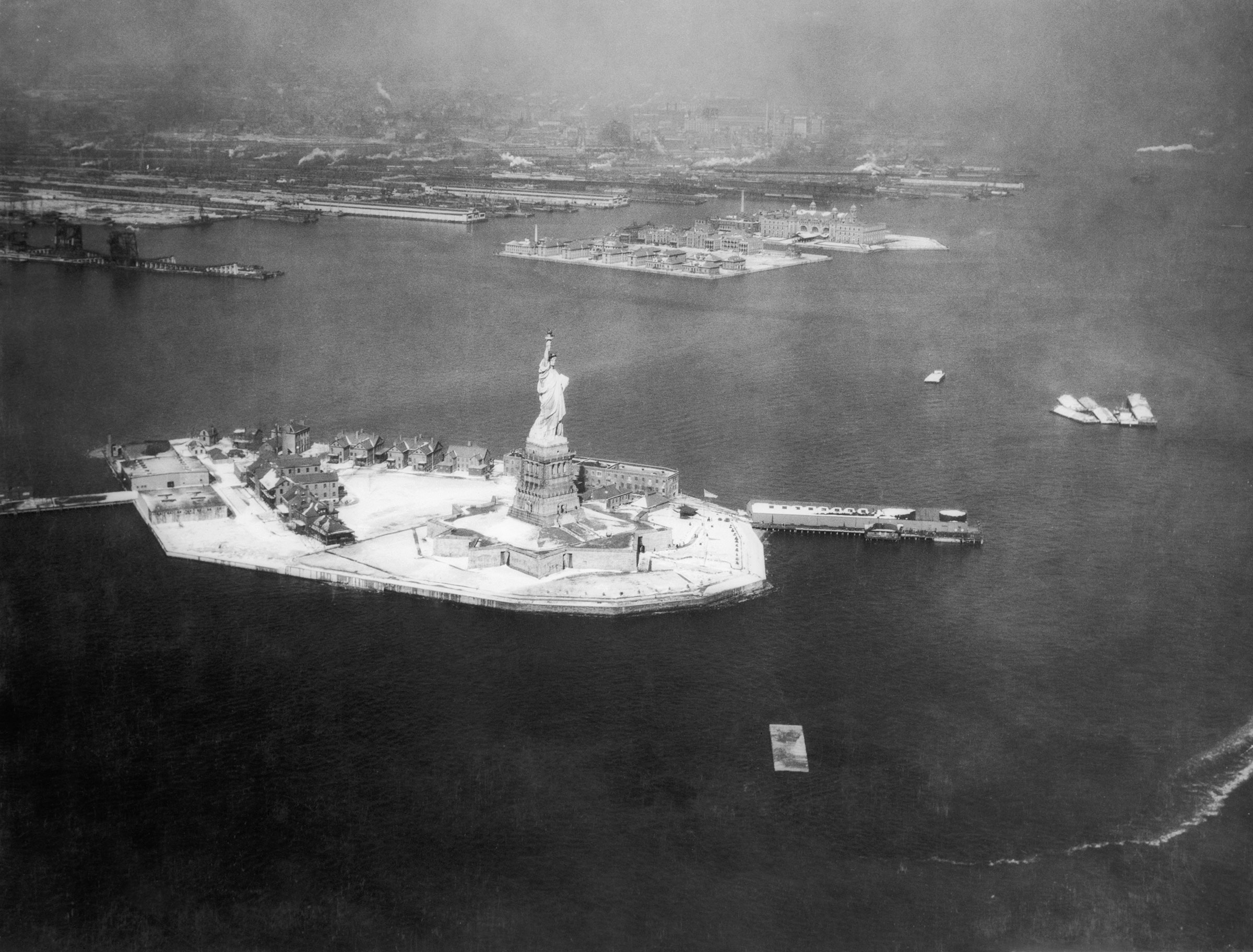 Aerial view of the Statue of Liberty, with Ellis Island in the background, date unknown.